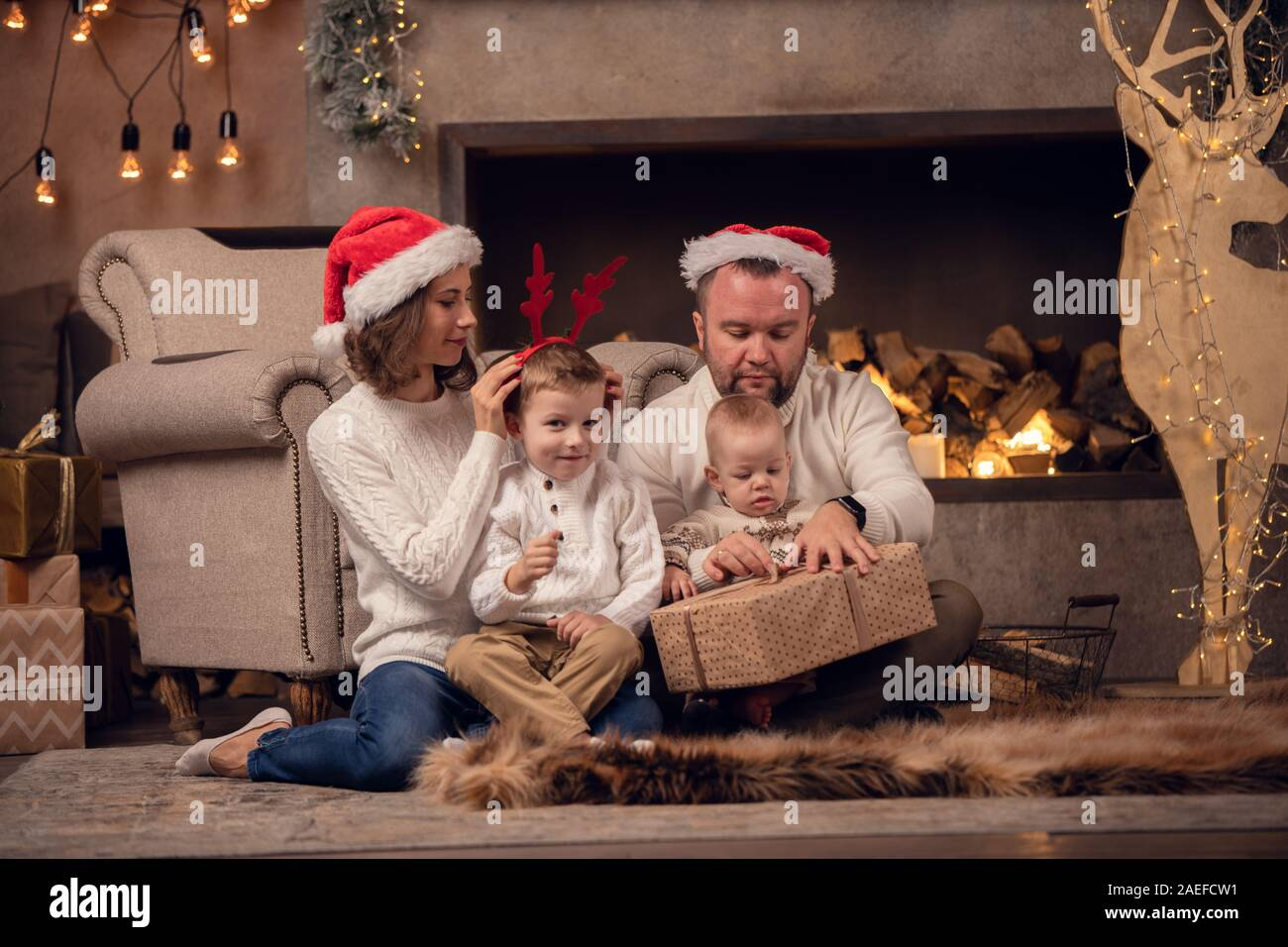 Picture of happy parents with son at fireplace, deer with garland in room with Christmas interior Stock Photo
