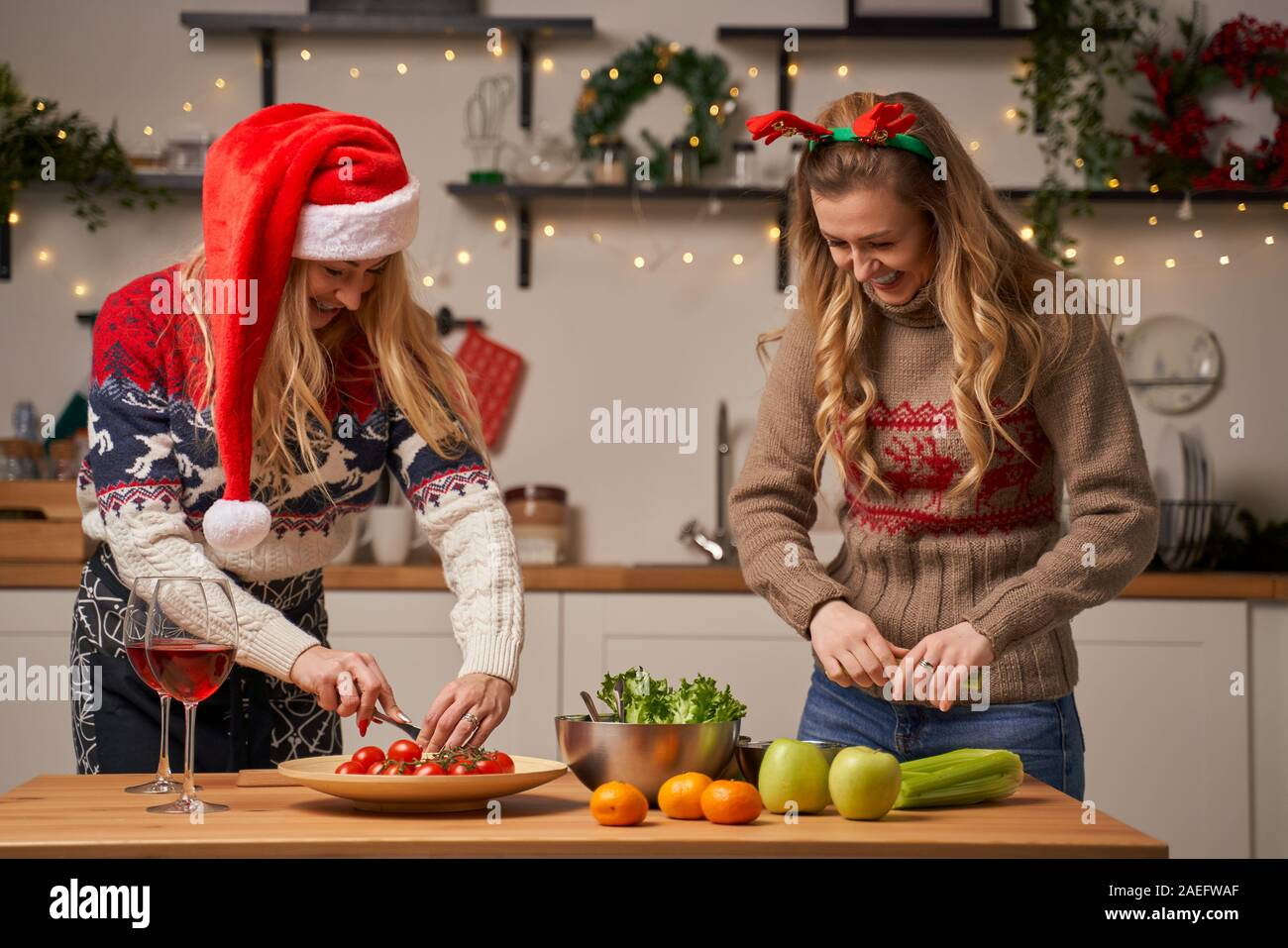 Two Blonde Women Prepare Food For New Year In Kitchen Decorated With Christmas Wreaths And Garlands Stock Photo Alamy