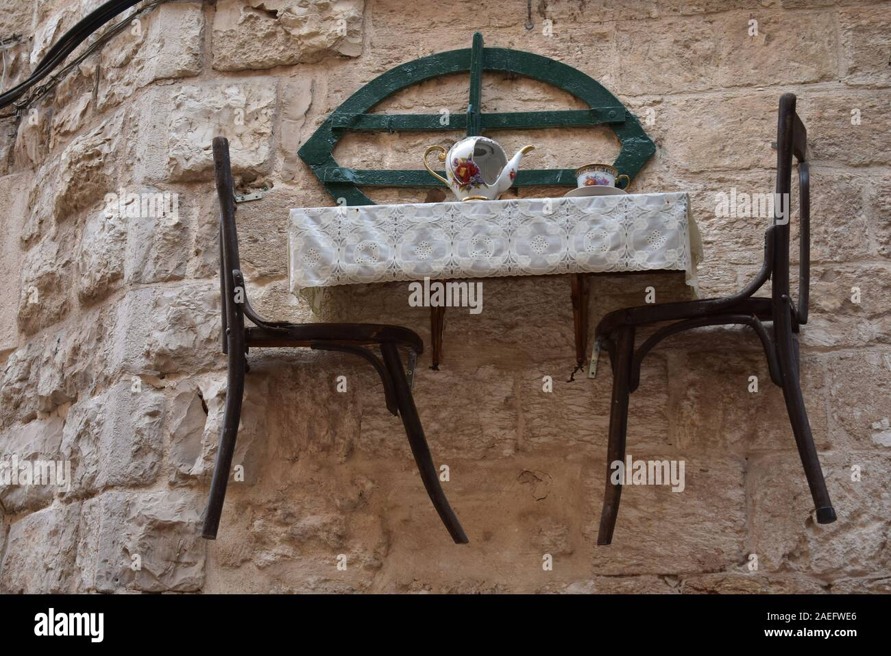 Table and Chairs hanging from a stone wall in Nazareth Israel Stock Photo