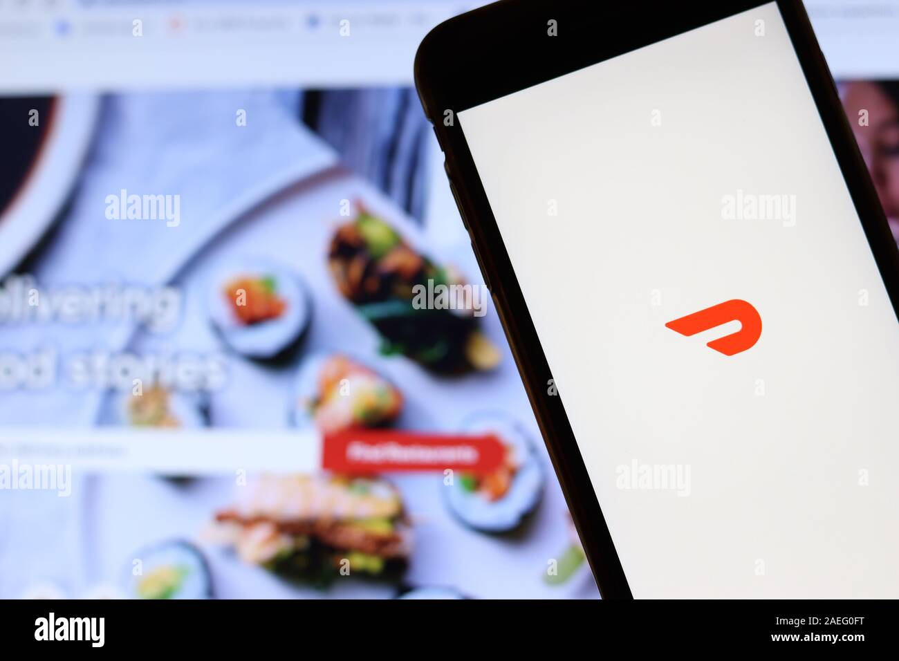 Los Angeles, California, USA - 21 November 2019: Doordash logo on phone screen with icon on laptop on blurry background, Illustrative Editorial. Stock Photo