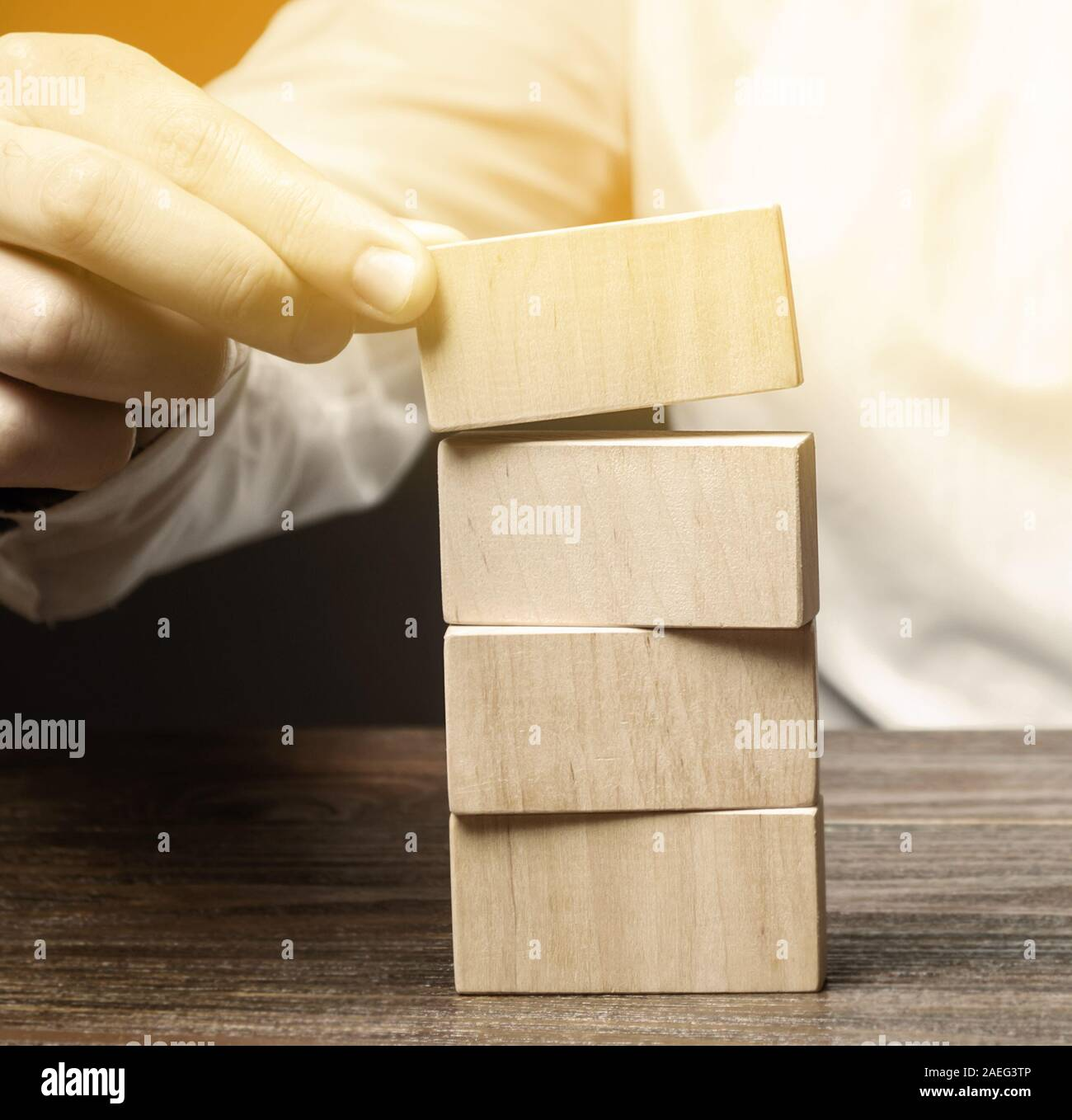 Businessman puts wooden blocks. Business management concept. Planning and strategy. Setting and achieving goals. Business stability. Road map. Stock Photo