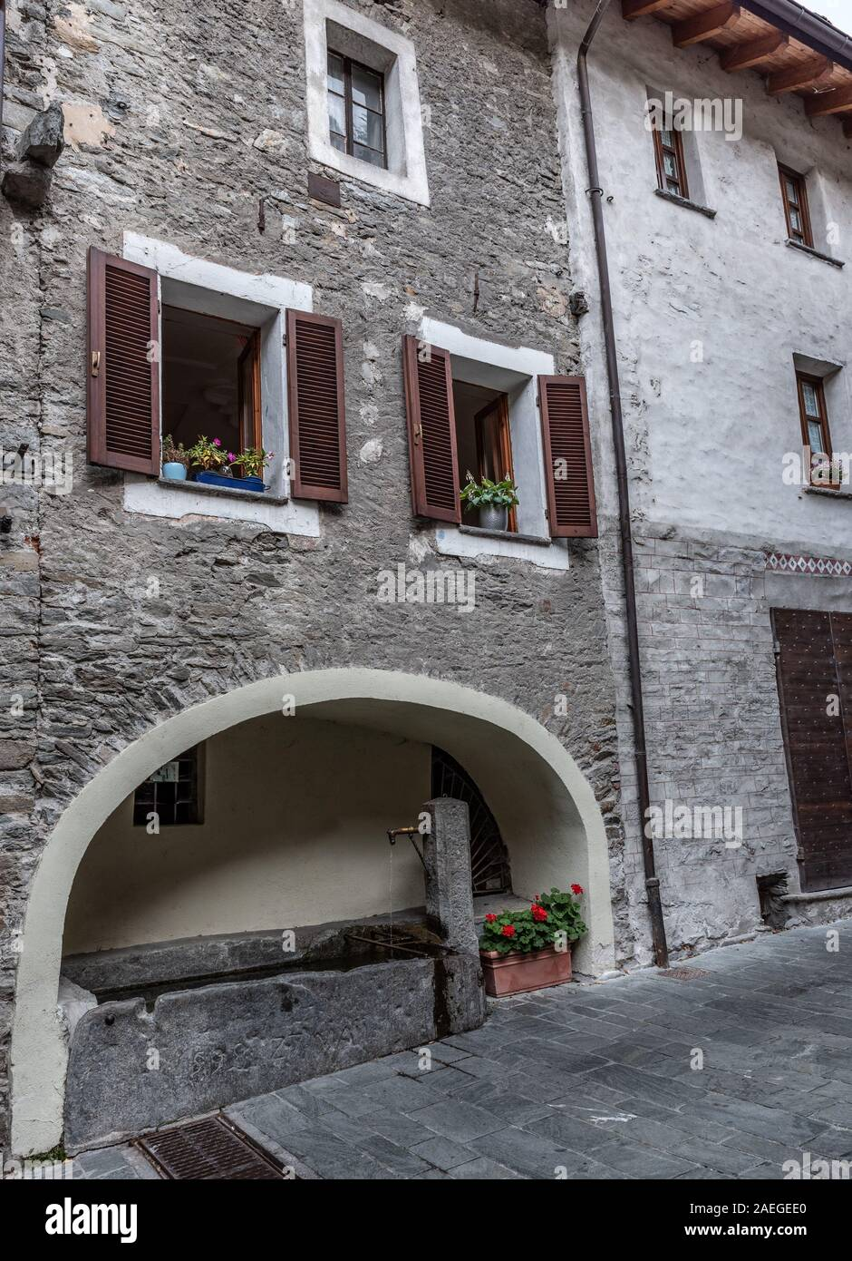 Ancient fountain in the medieval village of Bard in Valle D'Aosta, vertical image Stock Photo