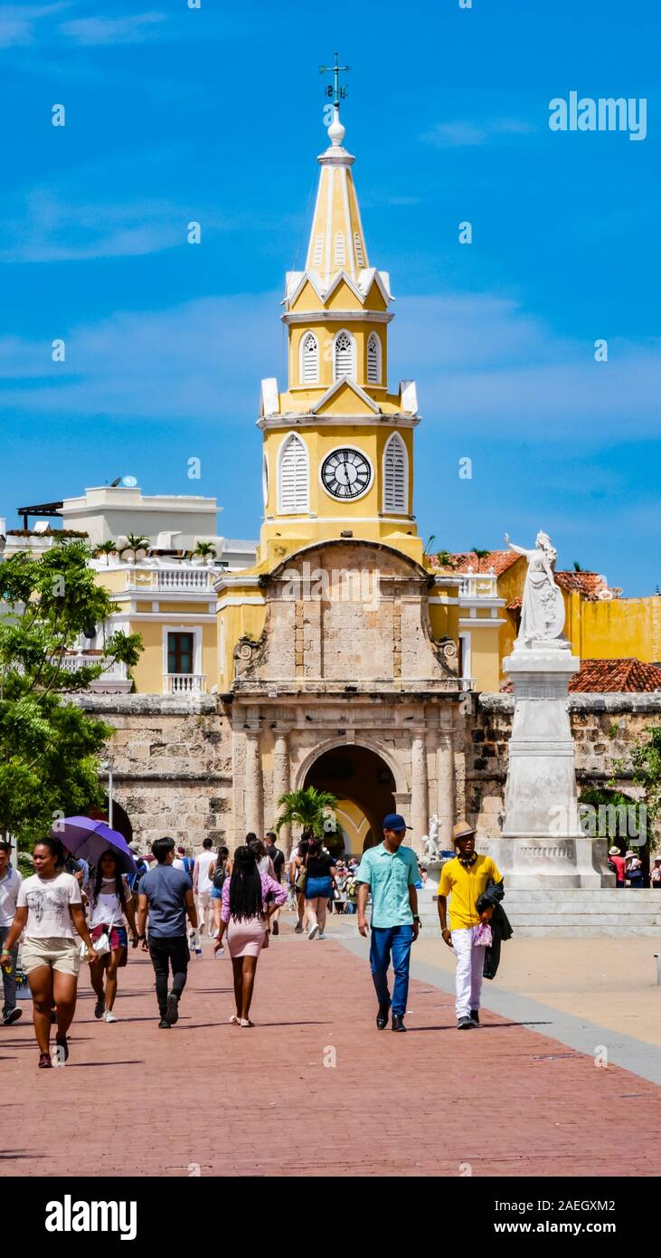 Locals walking in front of the clock tower gate which is  the main entrance into the old city of Cartagena Stock Photo