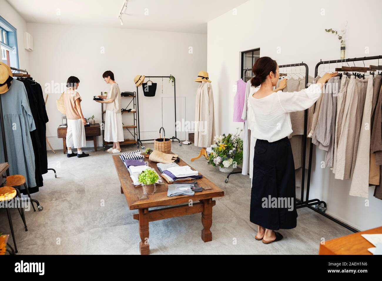 Three Japanese Women Standing In A Small Fashion Boutique Looking At Clothing On Rails Stock Photo Alamy