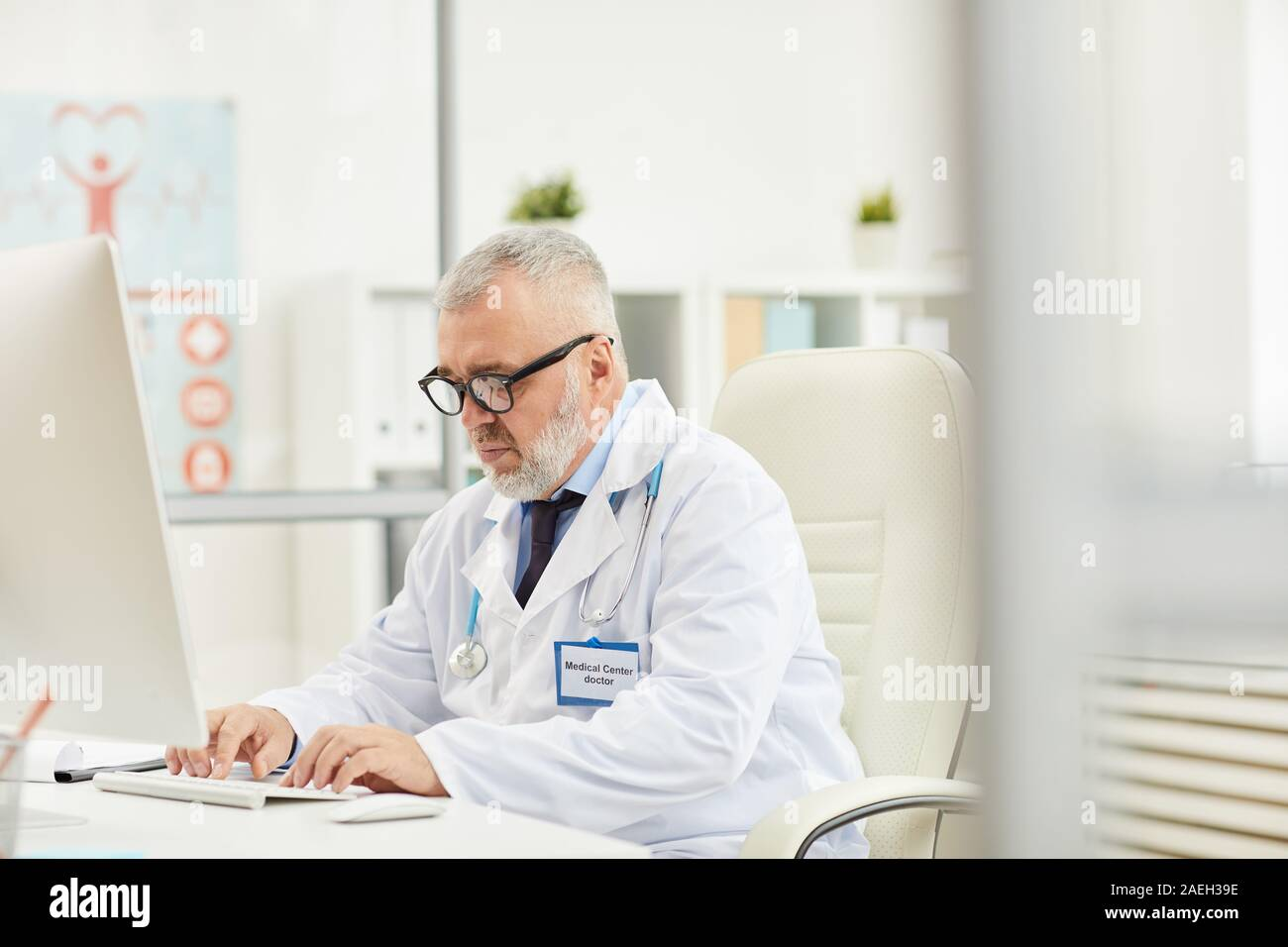 Serious mature medical professional sitting at the table and working on computer at his office Stock Photo