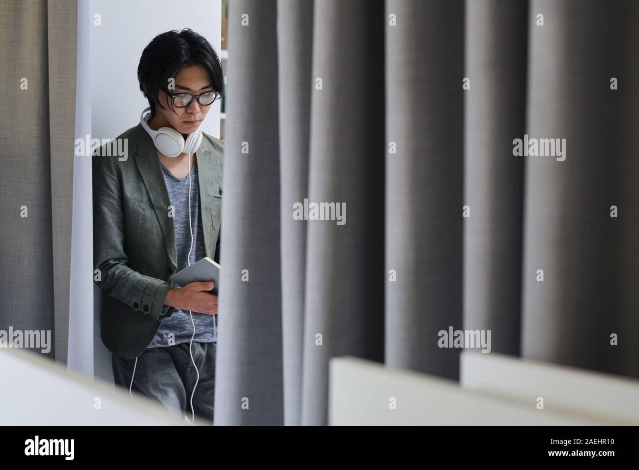 Asian young man in eyeglasses and with headphones busy reading a book Stock Photo