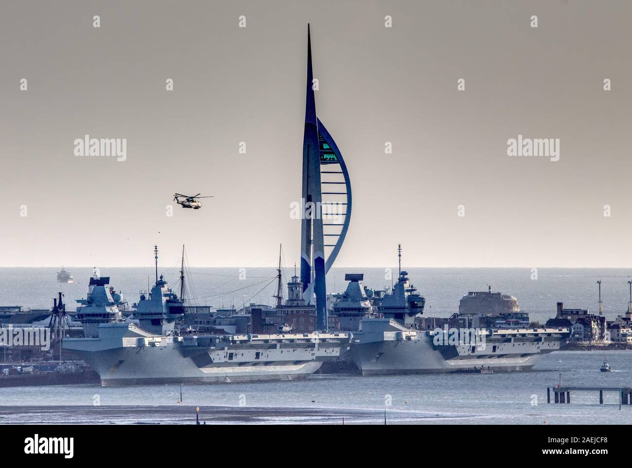 AJAXNETPHOTO. 9th December, 2019. PORTSMOUTH, ENGLAND. - Royal Navy's Sister Ships - HMS Queen Elizabeth (left) docked ahead of sister-ship HMS Prince of Wales today at Portsmouth Naval Base after returning from aviation exercises off the East Coast of the USA with one faulty Lightning F35B fighter jet parked on deck. 