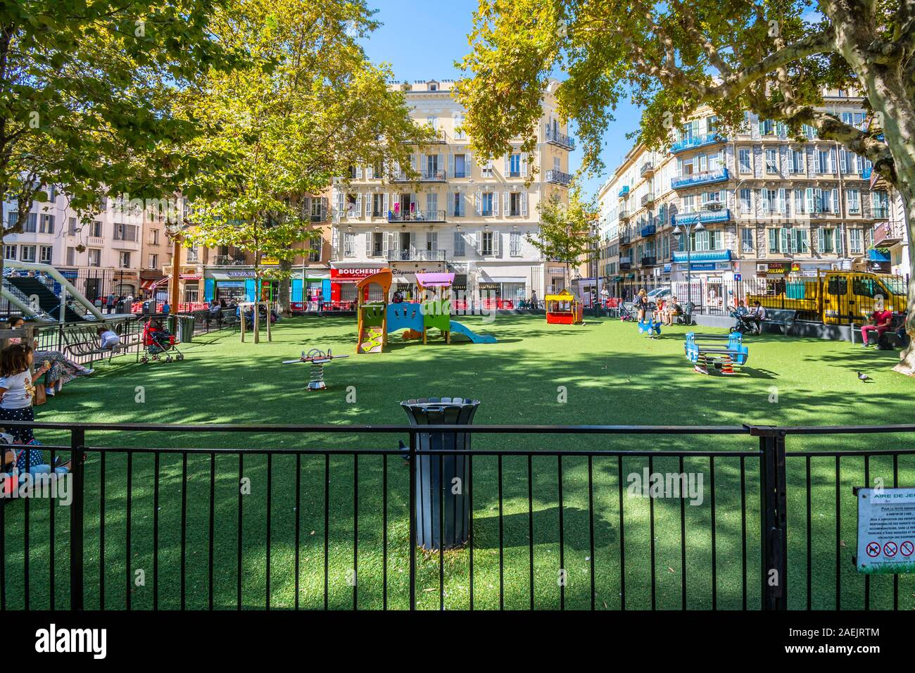 Children play in a small fenced playground school yard in the urban center of Nice, France. Stock Photo