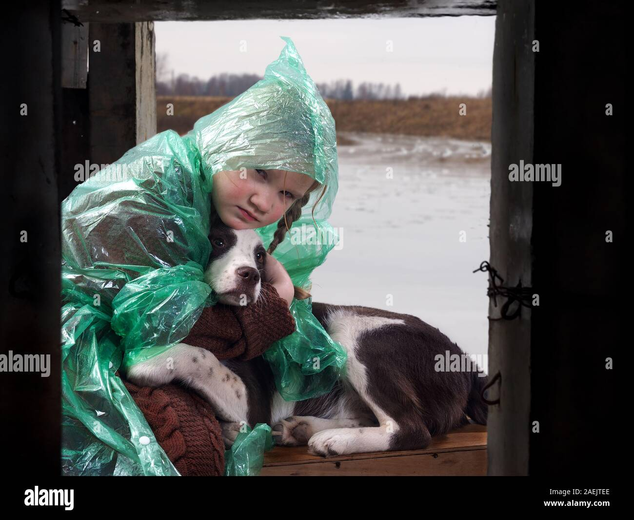 A child and a dog in a flood disaster area. The girl was crying. Waiting for help rescuers under the bridge Stock Photo