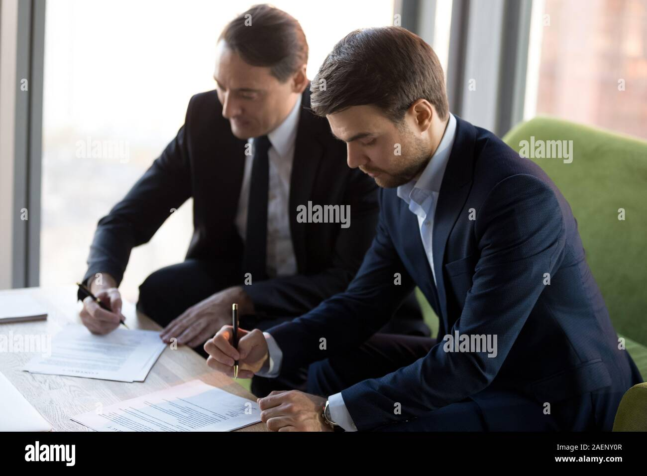 Successful businessmen in suits signing contract, partnership agreement Stock Photo