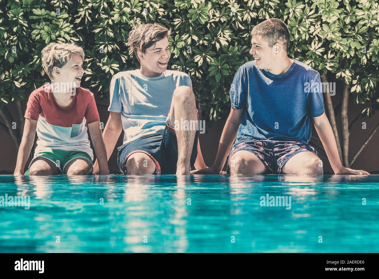 Young male enjoying days off of school relaxing in the swimming pool. Smiling teenagers sitting on the edge of the pool. Happy people enjoy summer Stock Photo