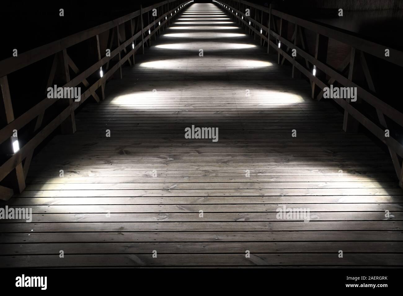 Wooden bridge illuminated by white circular lights at night, perspective Stock Photo