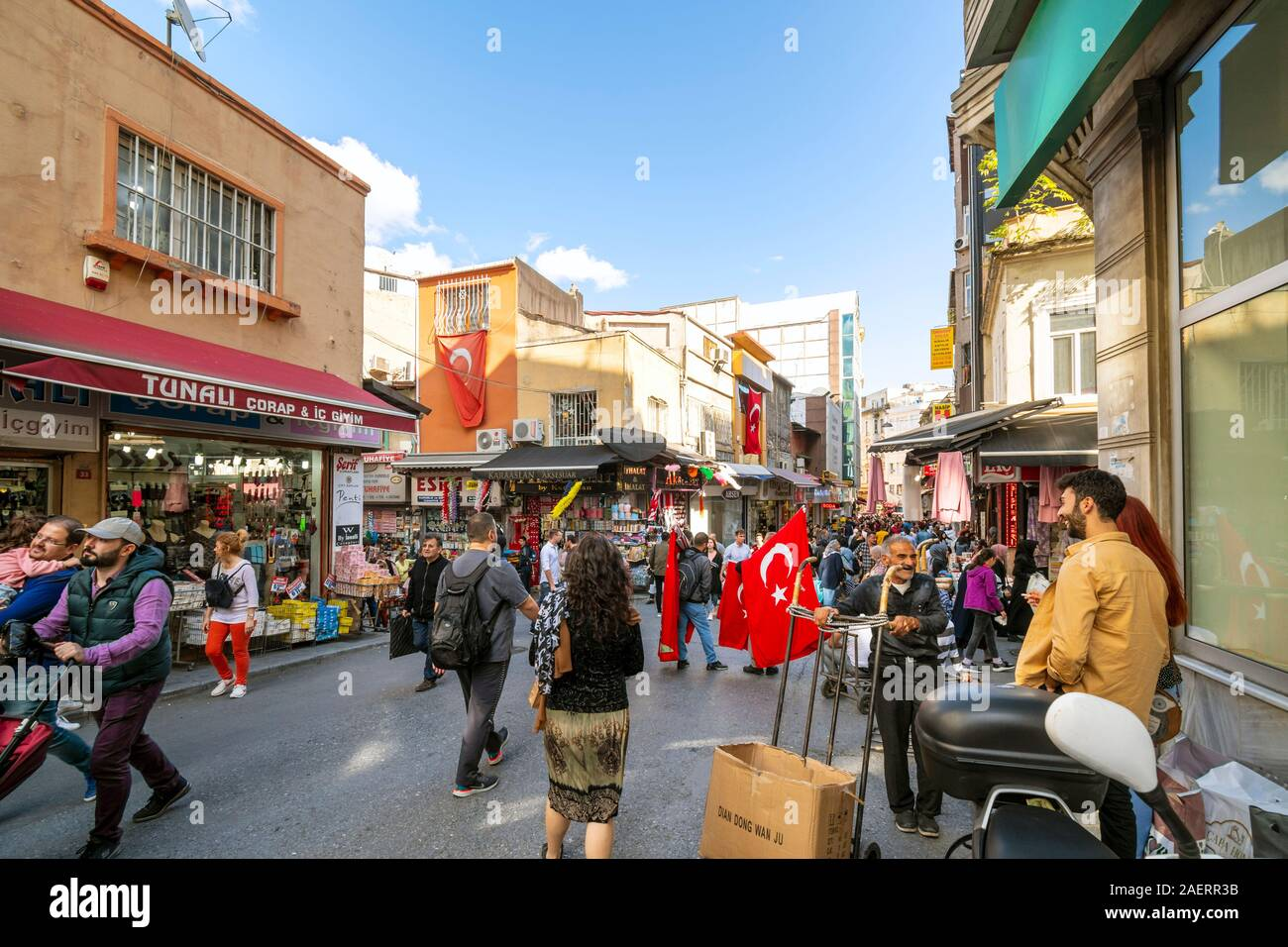 Local Turks shopping the large Eminonu outdoor market bazaar as they walk near a flying Turkish Flag in Istanbul, Turkey Stock Photo