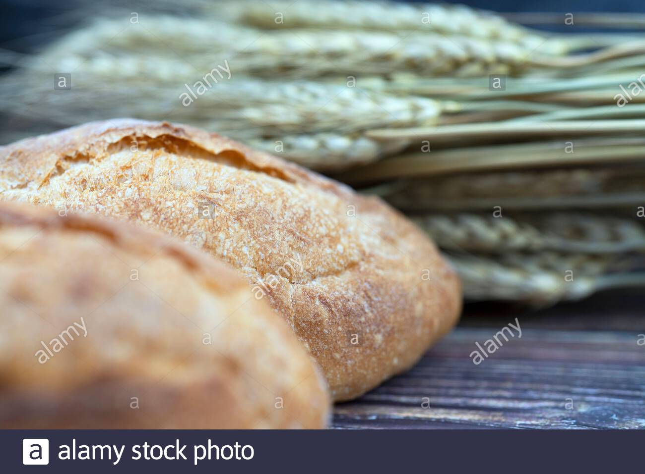 selective foxus of bread and wheat on  wood table for background Stock Photo