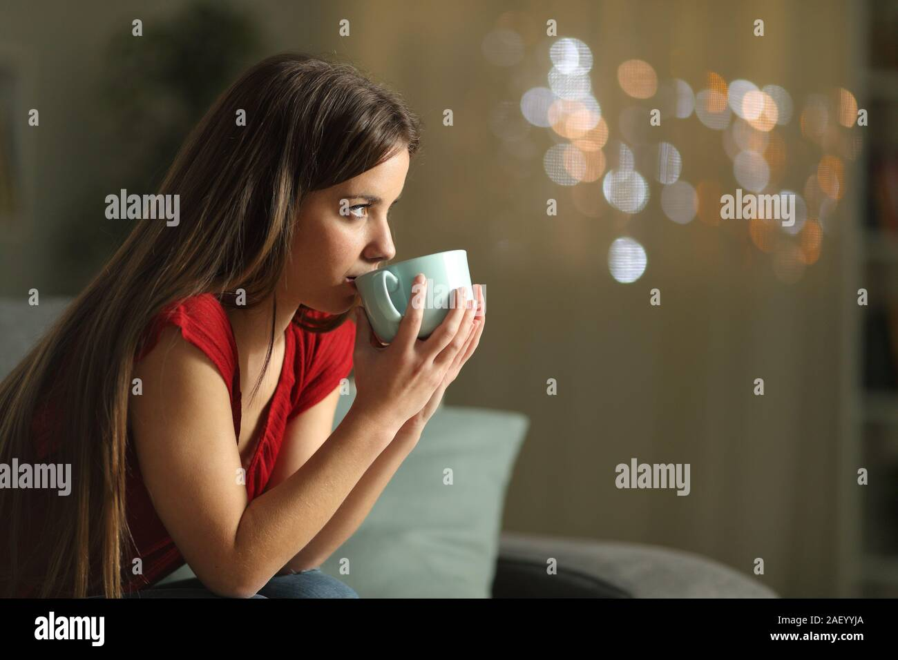 Side view portrait of a woman looking away drinking coffee sitting on a couch in the night at home Stock Photo