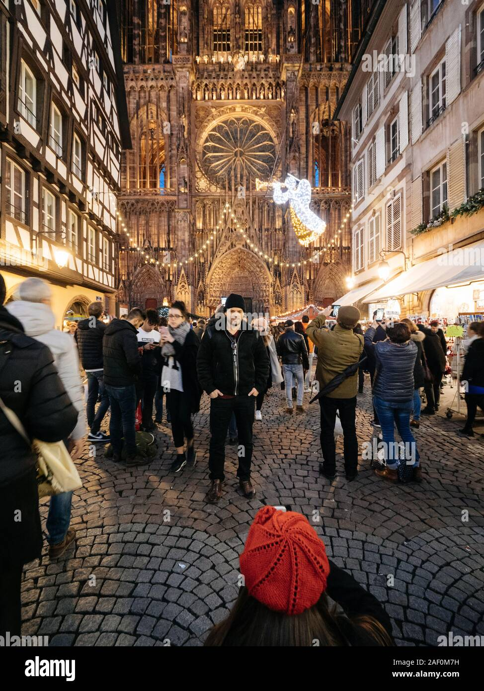 Strasbourg France Dec 24 2018 Wide Angle Lens Over Rear View Of Woman Wearing Red Beret Hat Taking A Memory Photo Of Her Boyfriend In Front Of The Notre Dame De Strasbourg