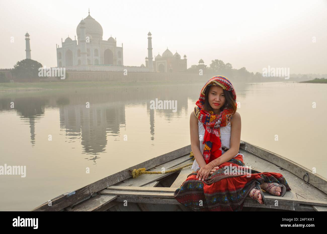 A woman watching sunset over Taj Mahal (Agra, India) from a wooden boat. Stock Photo