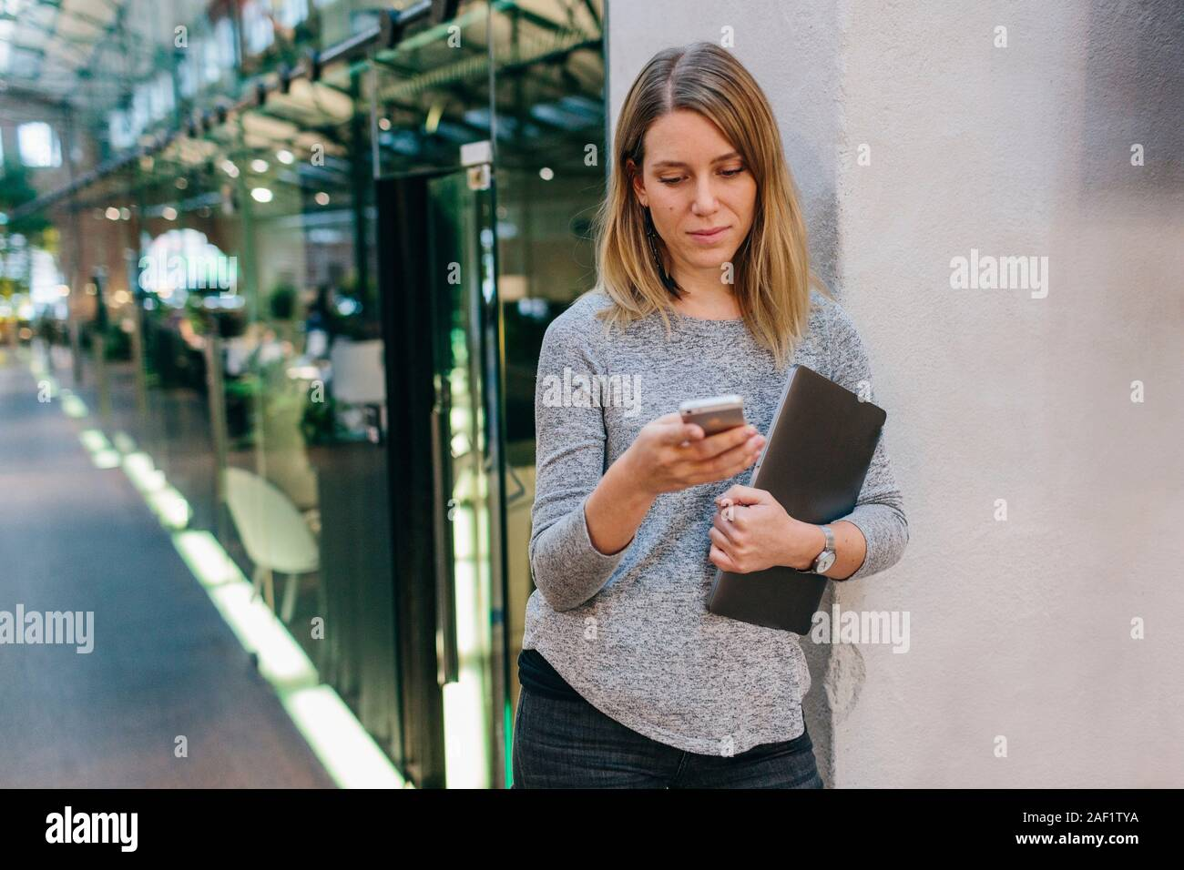 Woman in office corridor using cell phone Stock Photo
