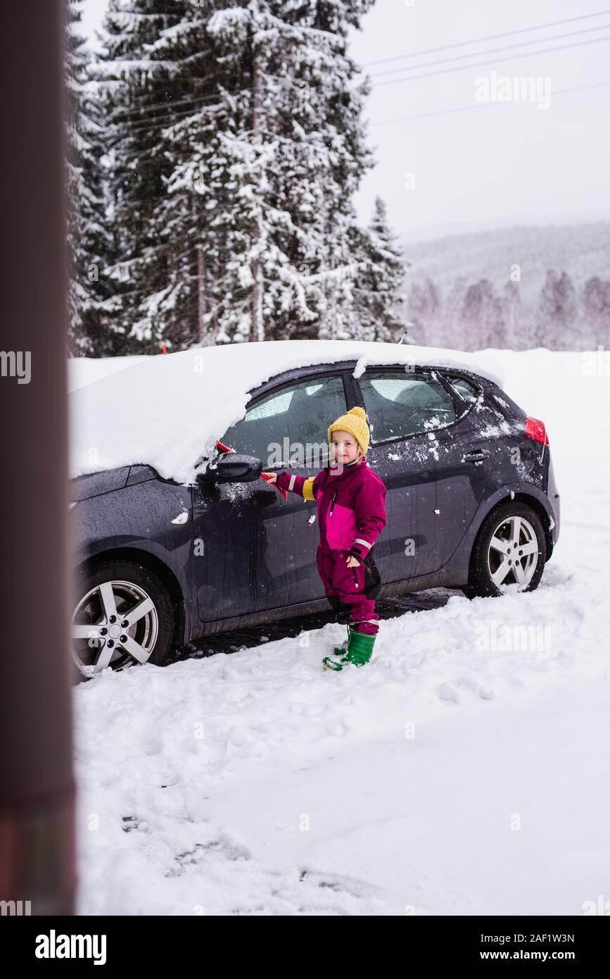 Girl brushing snow from car Stock Photo