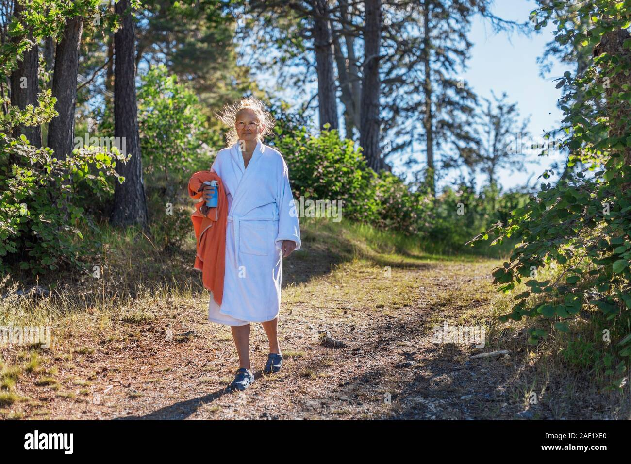 Woman wearing dressing gown holding towel Stock Photo