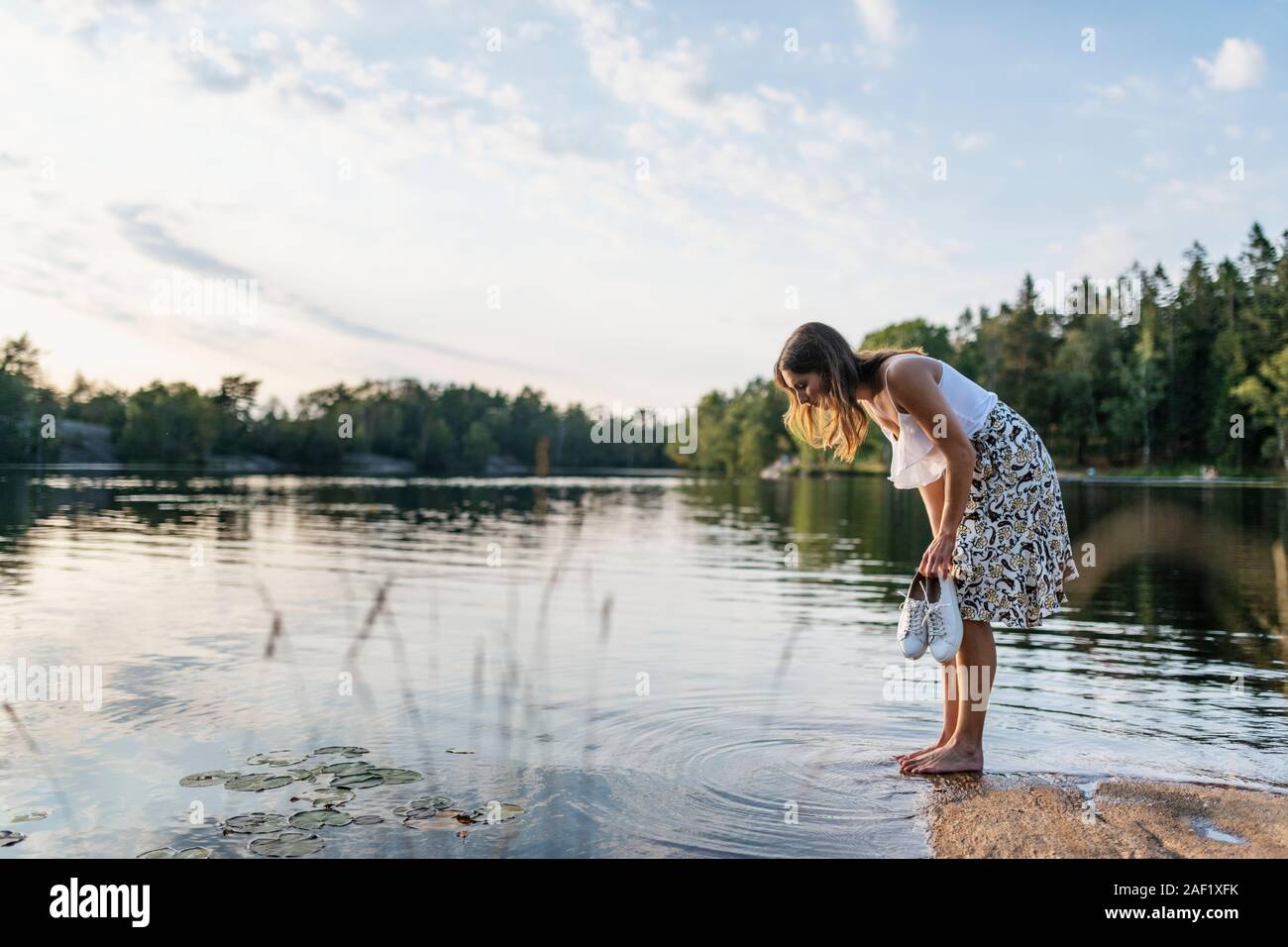 Woman looking into lake Stock Photo