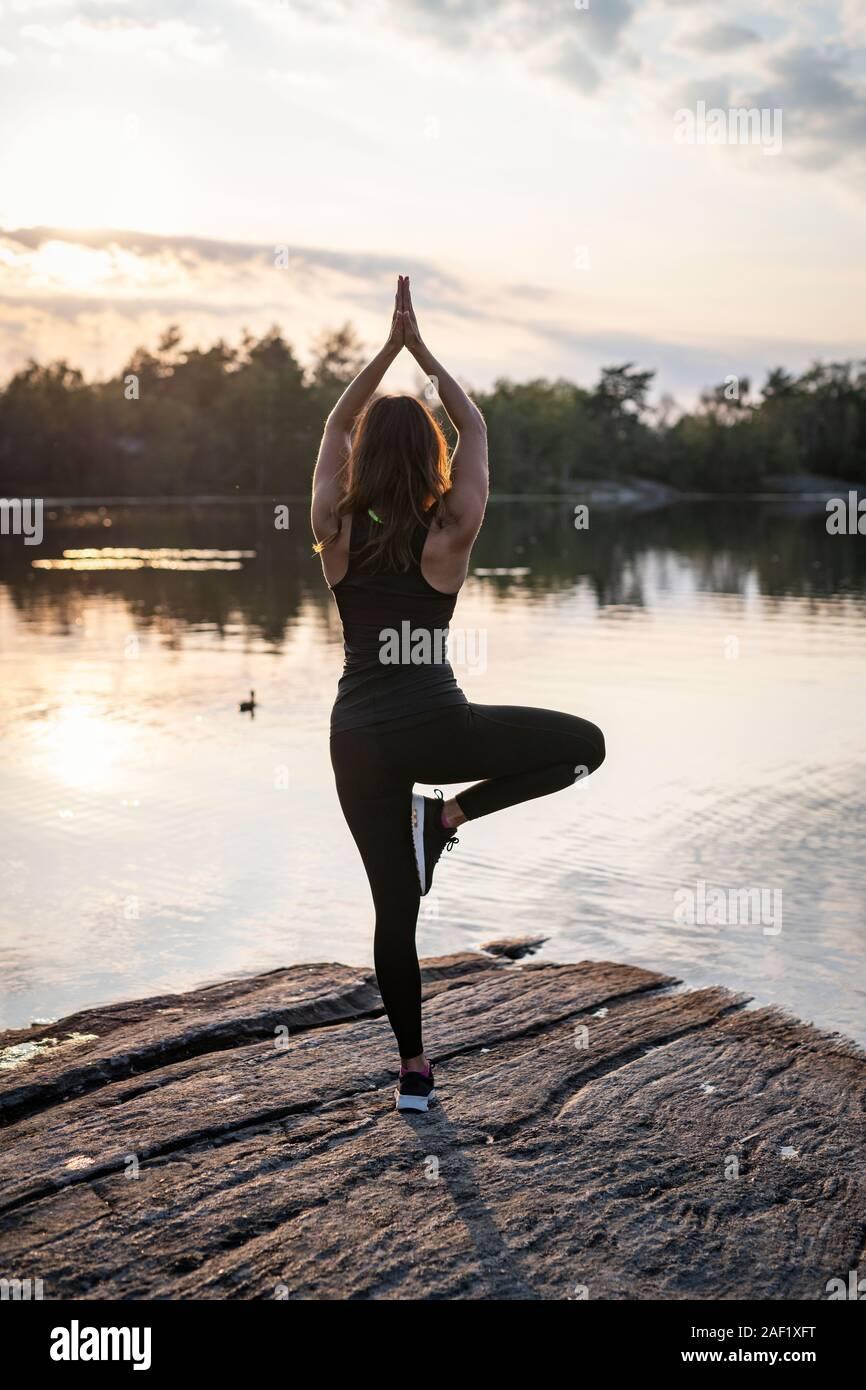 Woman at lake doing yoga Stock Photo