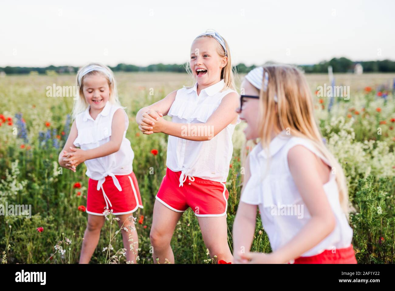 Happy sisters on meadow Stock Photo