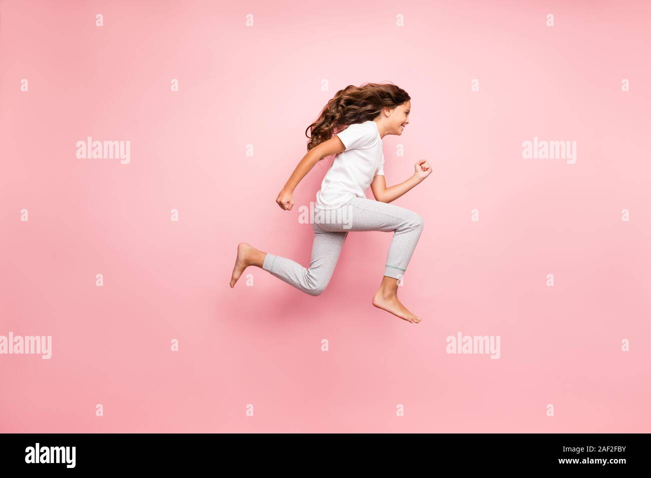 Full length body size side profile photo of cheerful barefoot positive running urgent hurrying preteen wearing t-shirt isolated over pastel color Stock Photo