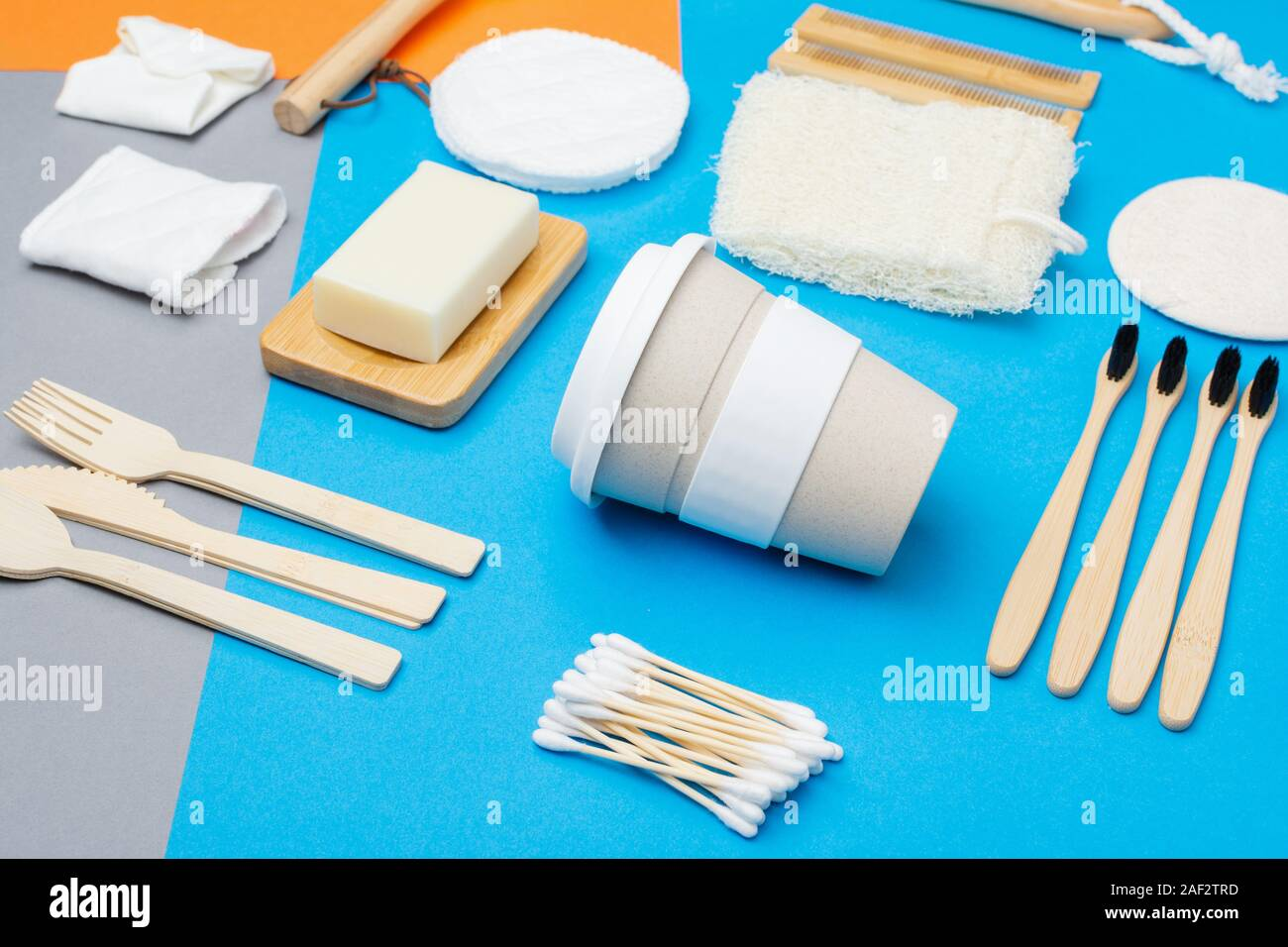 Zero waste eco friendly personal care products wooden brushes, bamboo toothbrushes, luffa, natural soaps, reusable coffee cup on colorful blue grey orange background, selective focus Stock Photo