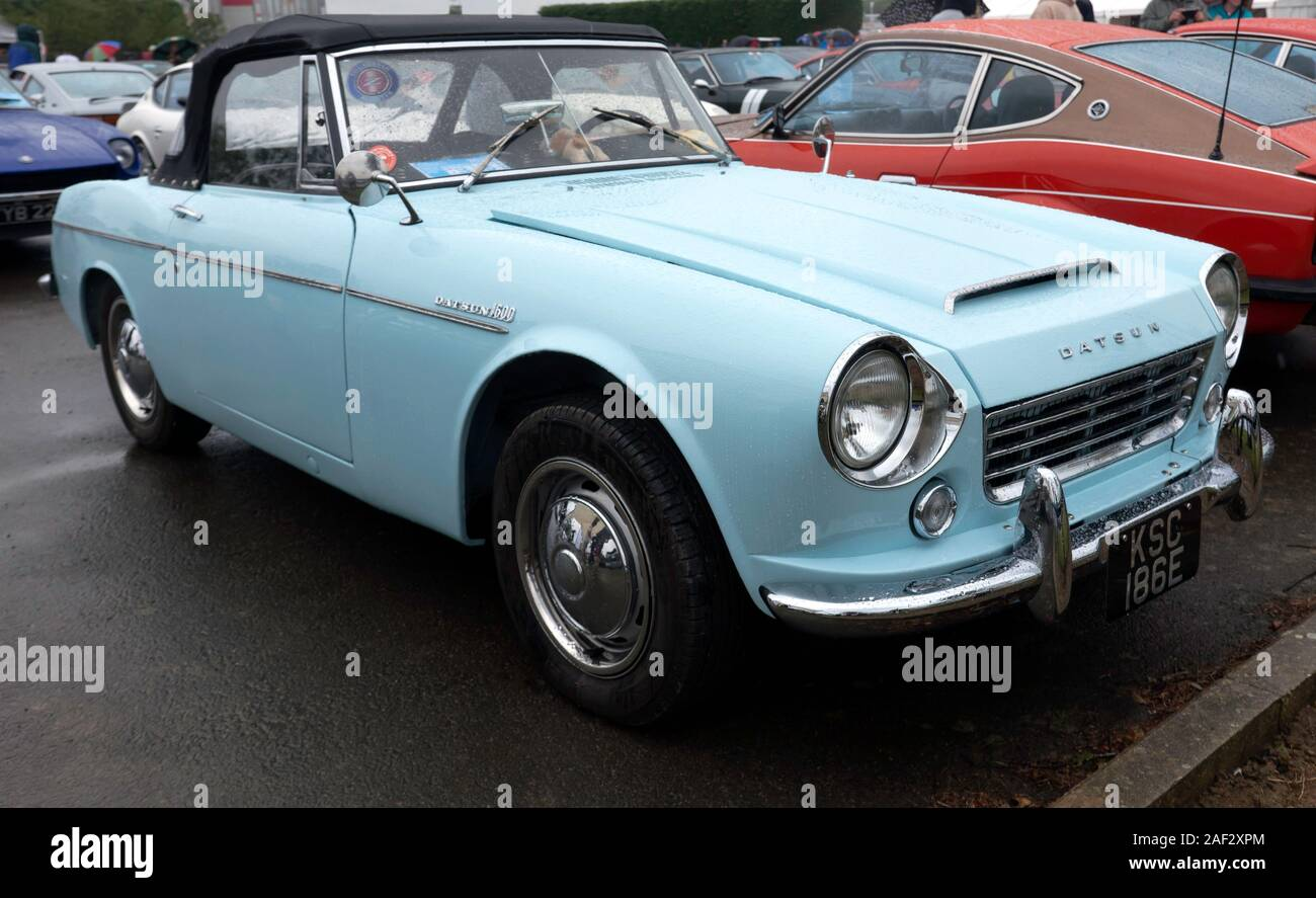 Three-quarter front view of a Blue,1967,  Datsun 1600 Roadster, on display in the Car Club Zone of the 2019 Silverstone Classic Stock Photo