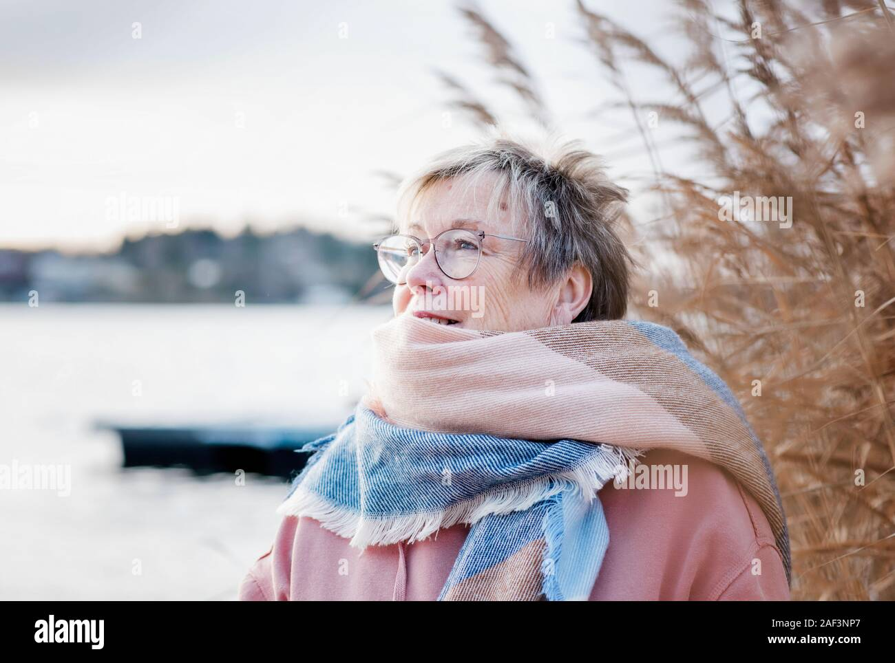 Portrait of woman in her 60's looking happy sitting outside in fall. Stock Photo