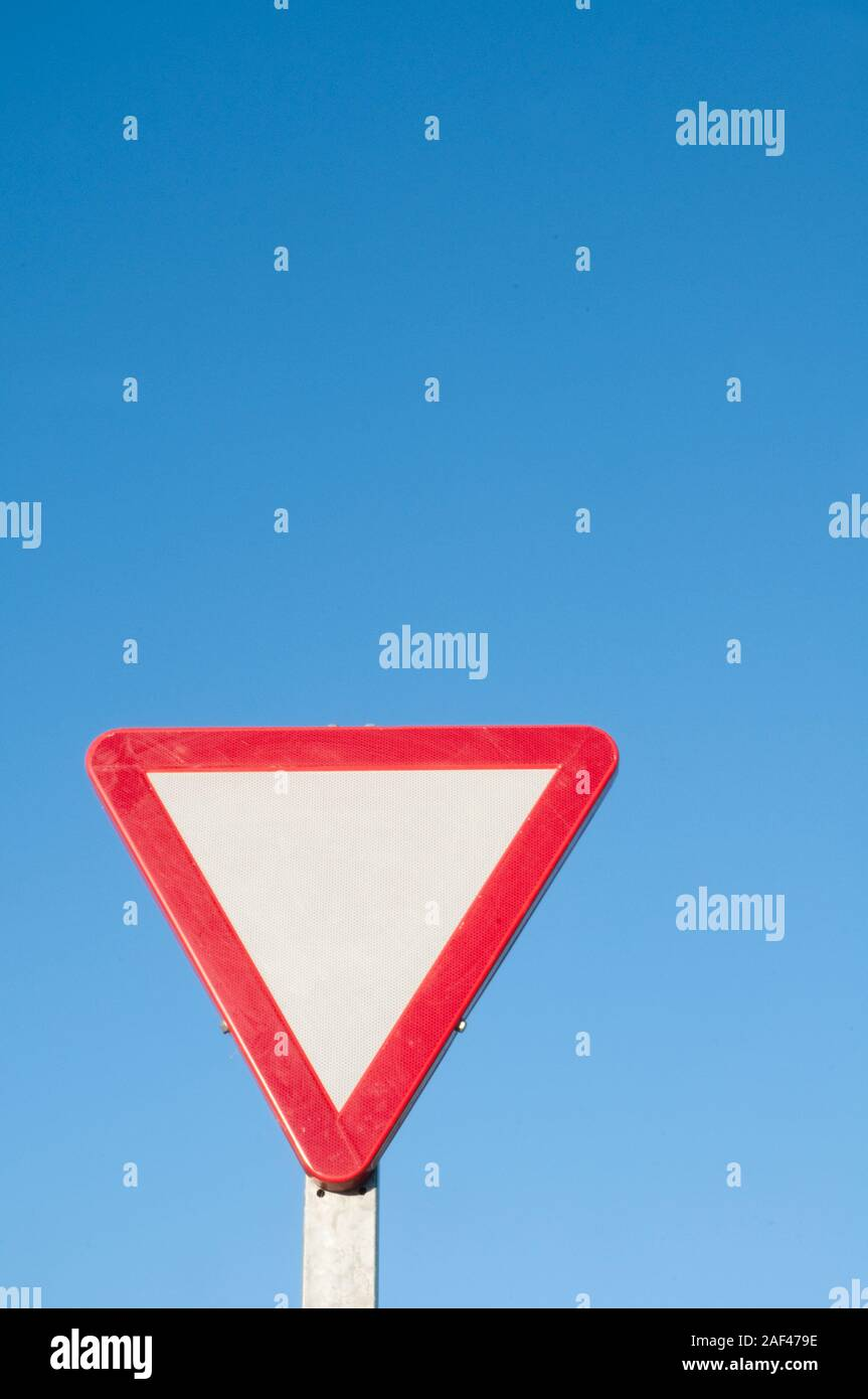 Give way signal against blue sky. Stock Photo