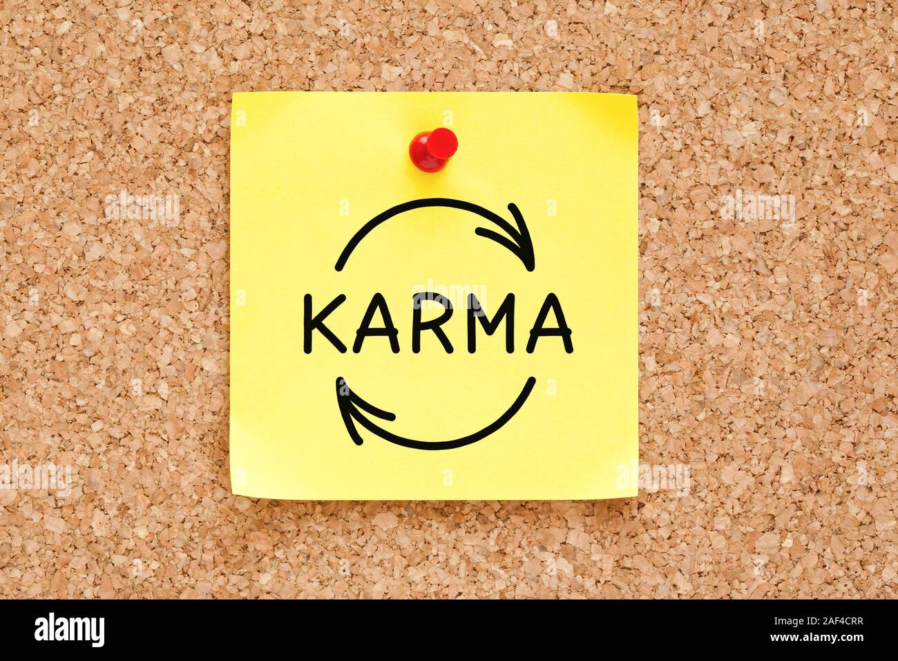 Hand drawing Karma cycle concept on yellow adhesive note pinned on cork bulletin board. Stock Photo