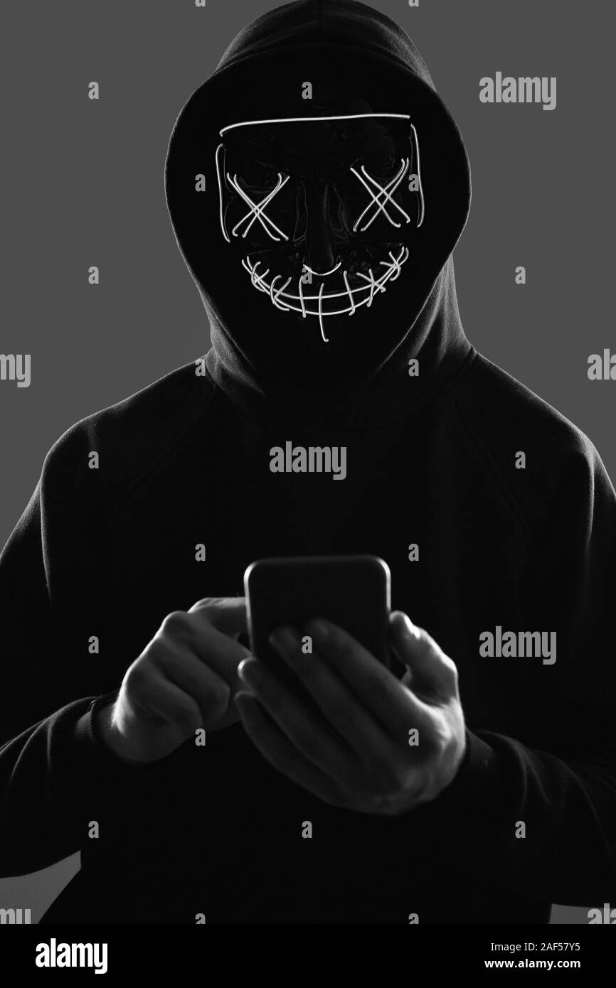 Portrait Of An Anonymous Man In A Black Hoodie And Neon Mask Hacking Into A Smartphone Studio Shot Stock Photo Alamy