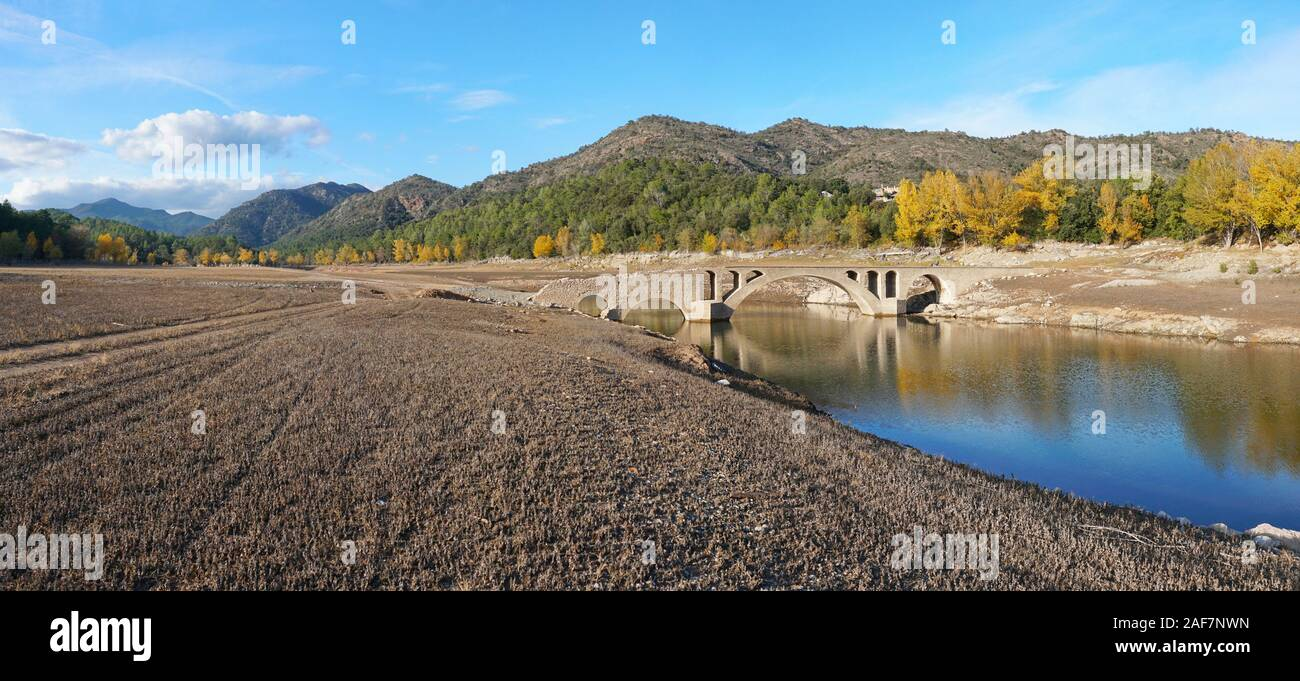 Spain, an old stone bridge in the reservoir of Boadella with a low water level, panoramic landscape, Catalonia, Girona province, Alt Emporda Stock Photo