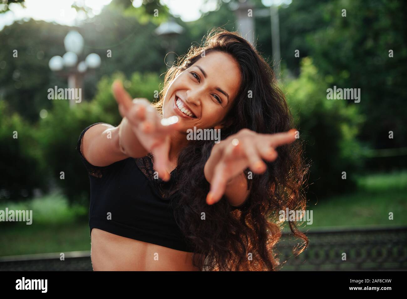 Full of life energy. Beautiful woman with curly black hair have good time in the city at daytime Stock Photo