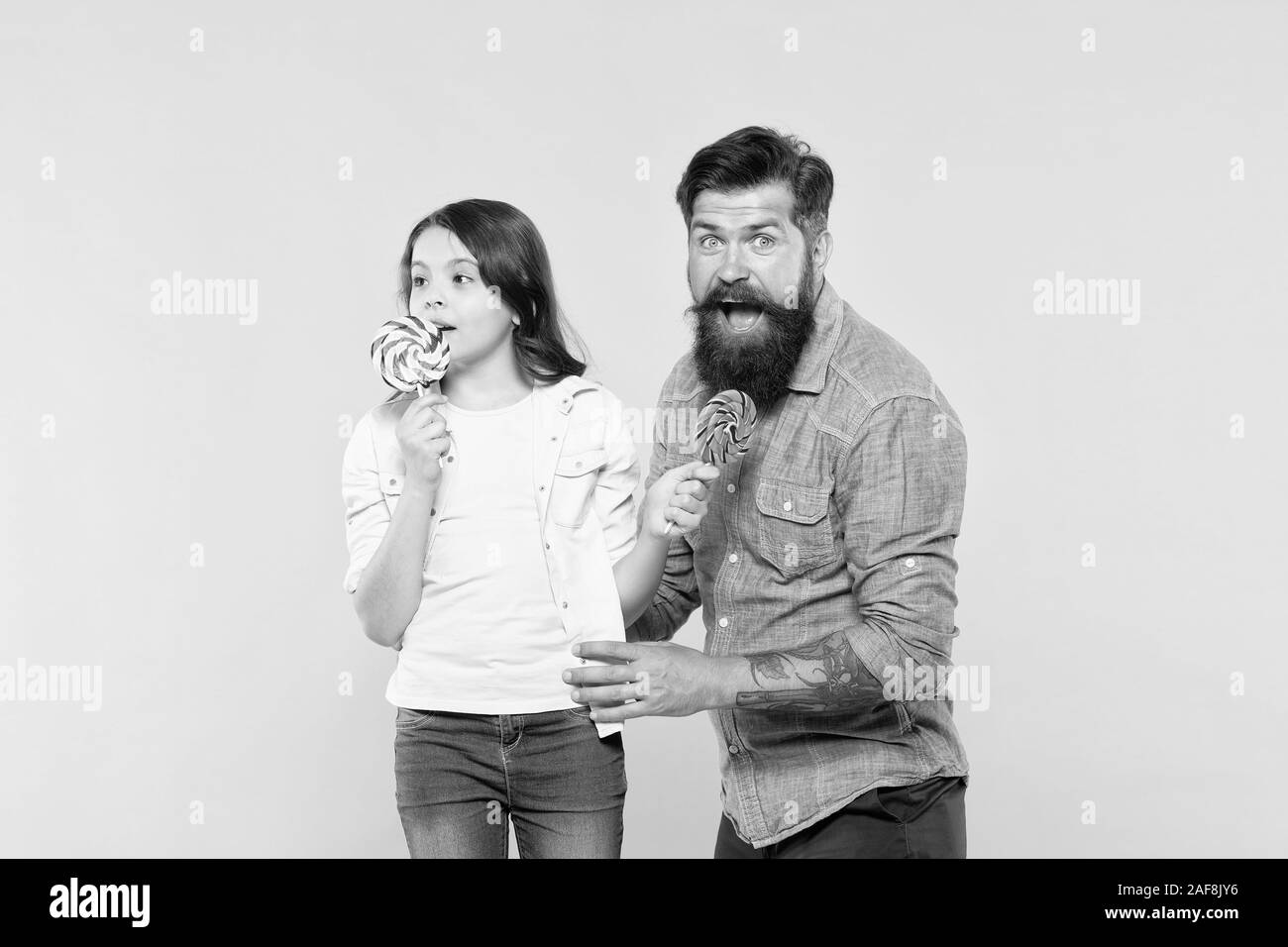 candy shop. happy childhood. Daughter and dad eat candy. bearded hipster man is good father. little girl and dad hold colorful lollipop. summer vibes. happy family. cheerful about dessert. Stock Photo
