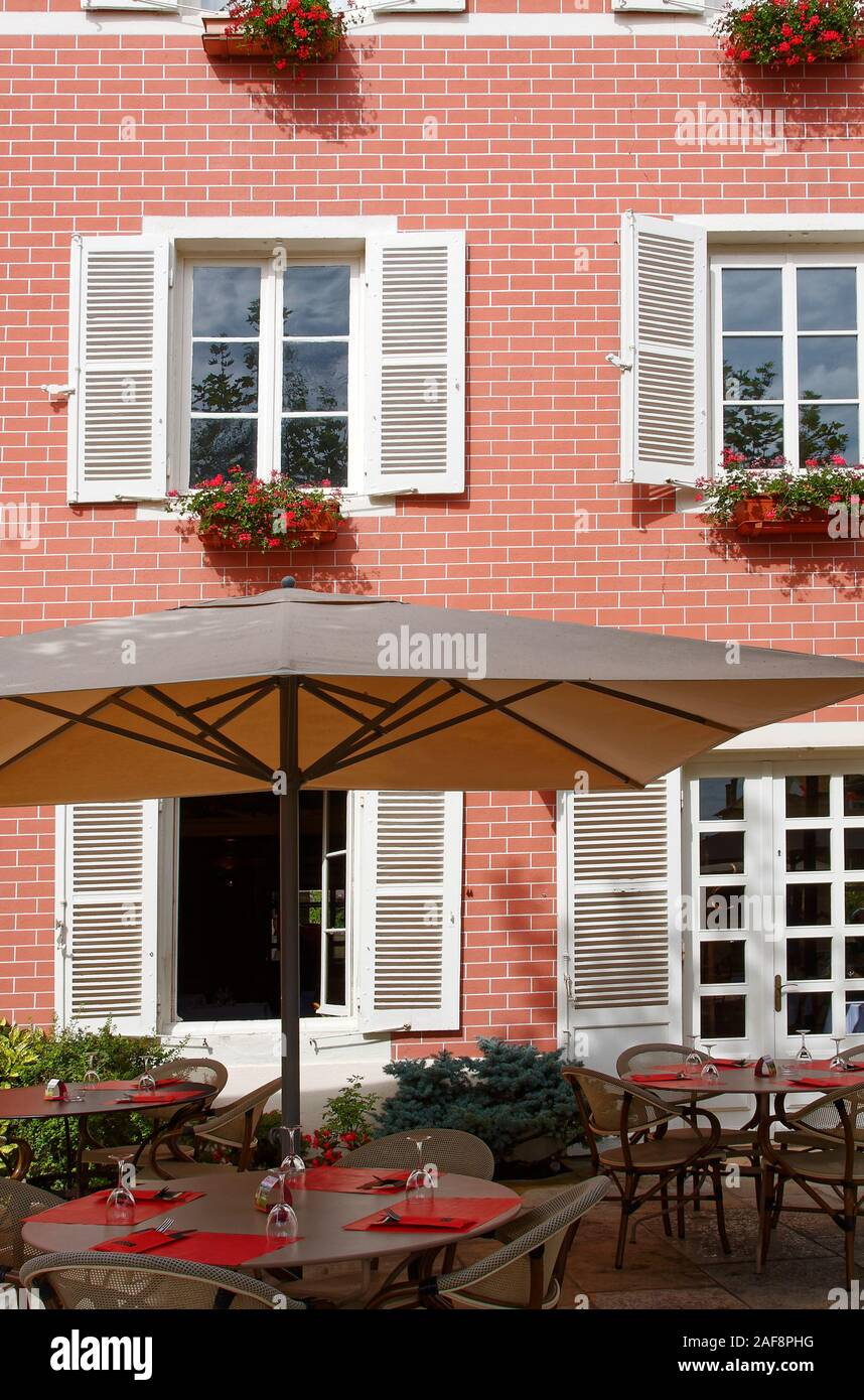 outdoor tables, set with placemats, wine glasses, umbrella, brick building, shutters, flower boxes, Georges du Boeuf Wine Museum and Winery; Beaujolai Stock Photo
