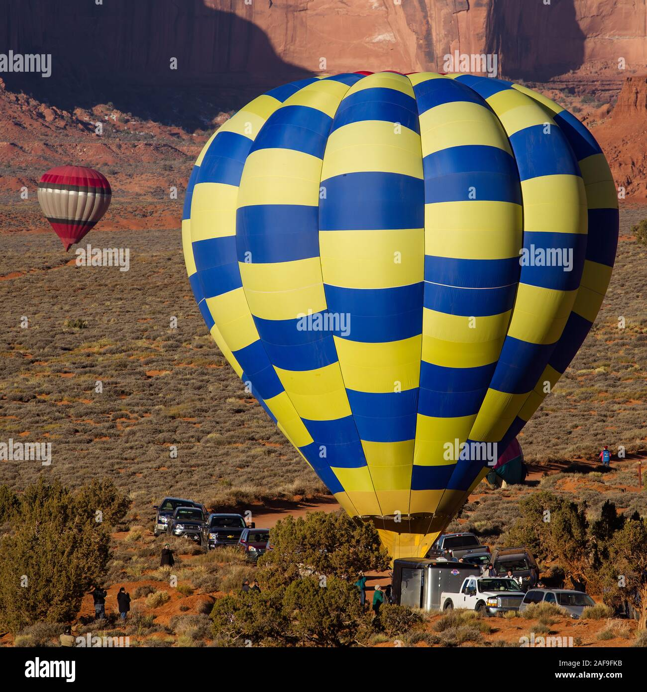 A team prepares for launch in the Monument Valley Navajo Tribal Park in Arizona.  In the background is another ballon ready to take flight. Stock Photo