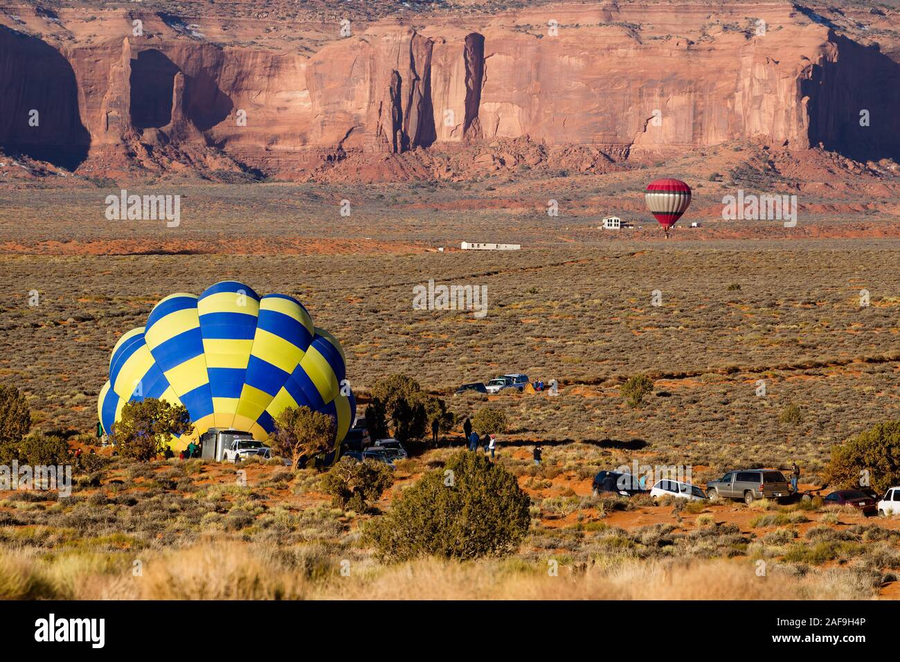 A team inflates a hot balloon in preparation for launch in the Monument Valley Navajo Tribal Park in Arizona.  Another balloon is takinf off in the ba Stock Photo