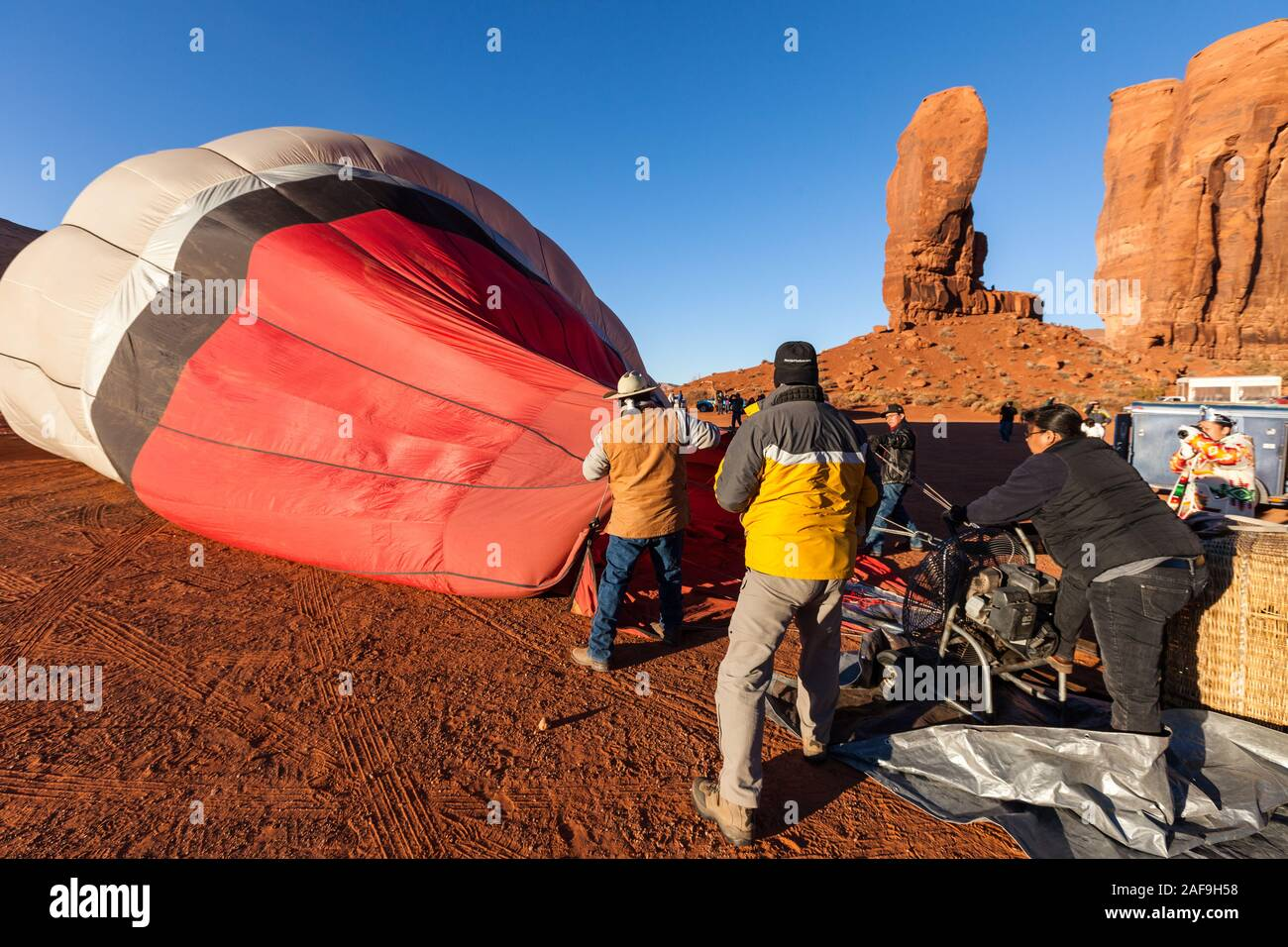 A team inflates a hot balloon in preparation for launch in the Monument Valley Navajo Tribal Park in Arizona.  In the background is the rock formation Stock Photo
