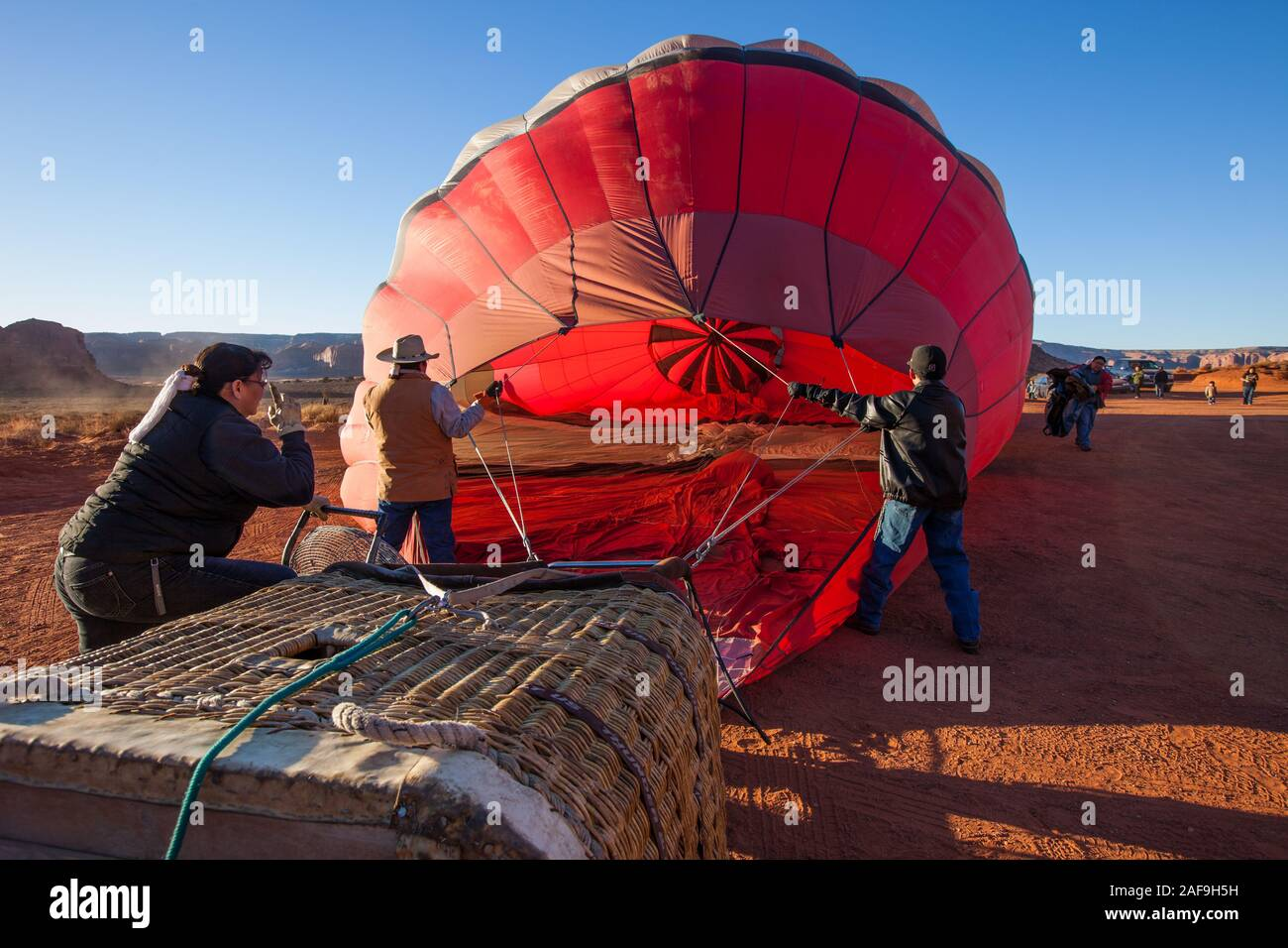 A team inflates a hot balloon in preparation for launch in the Monument Valley Navajo Tribal Park in Arizona. Stock Photo