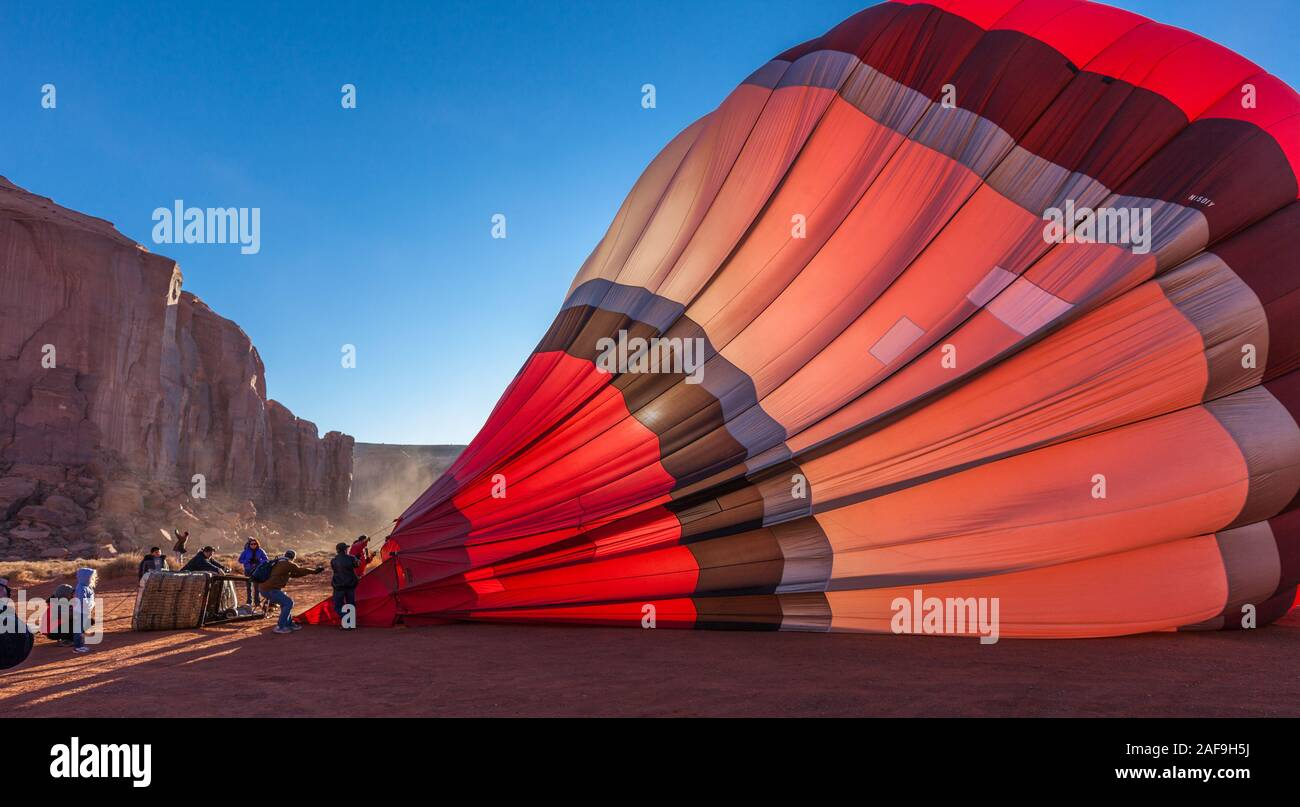 A ground crew inflates a hot balloon in preparation for launch in the Monument Valley Navajo Tribal Park in Arizona. Stock Photo