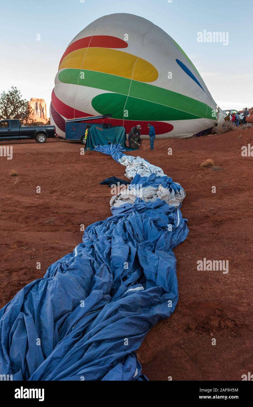 A hot air balloon is unfurled and rolled out on the ground as the team prepares to start inflating it, first with a powerful fan, and then the gas bur Stock Photo