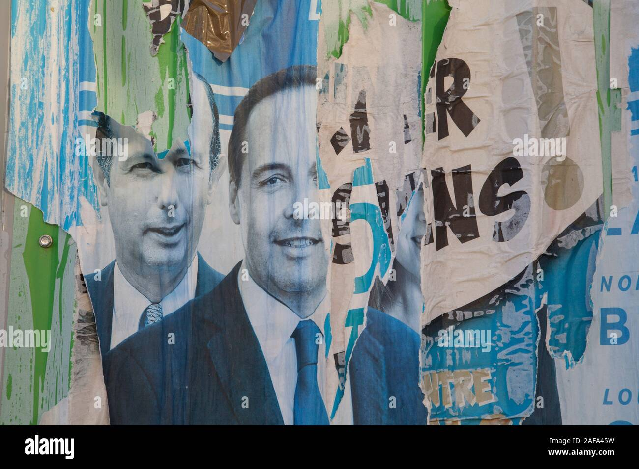 Torn political posters on a wall in Paris Stock Photo