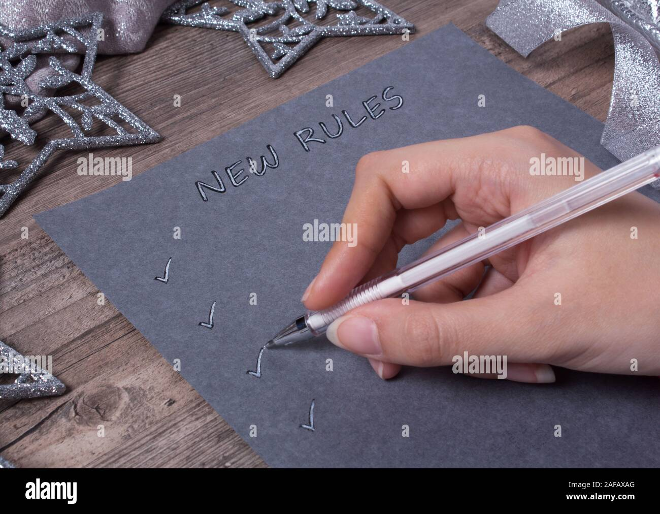A person writes words on grey paper. New year, new rules. Motivation, plan, schedule, task, new life. Christmas, holiday. Snowflakes and Christmas toy Stock Photo