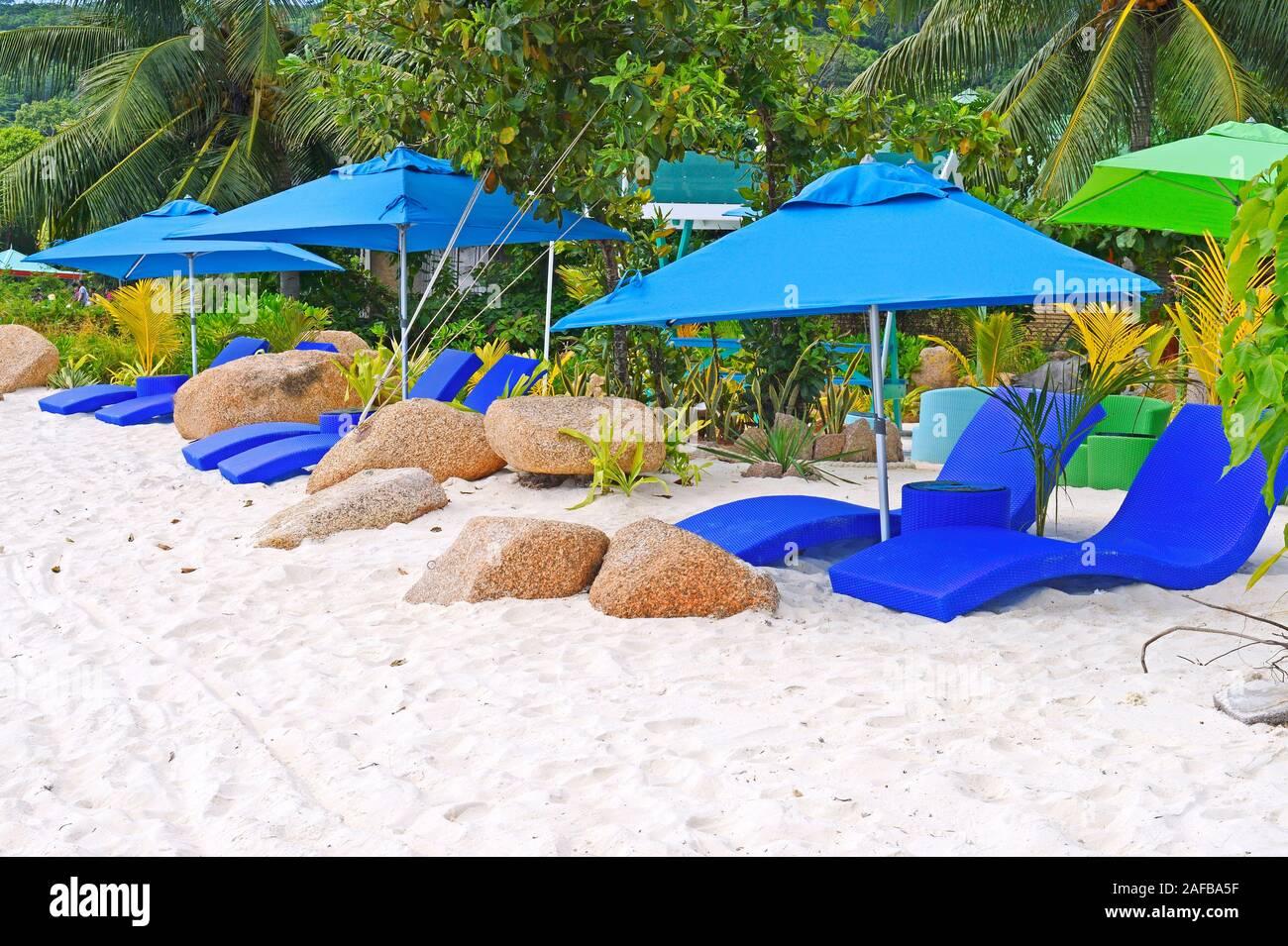 Sonnenschirme und Liegen eines Luyushotels auf der Insel  Insel La Digue,  Seychellen Stock Photo