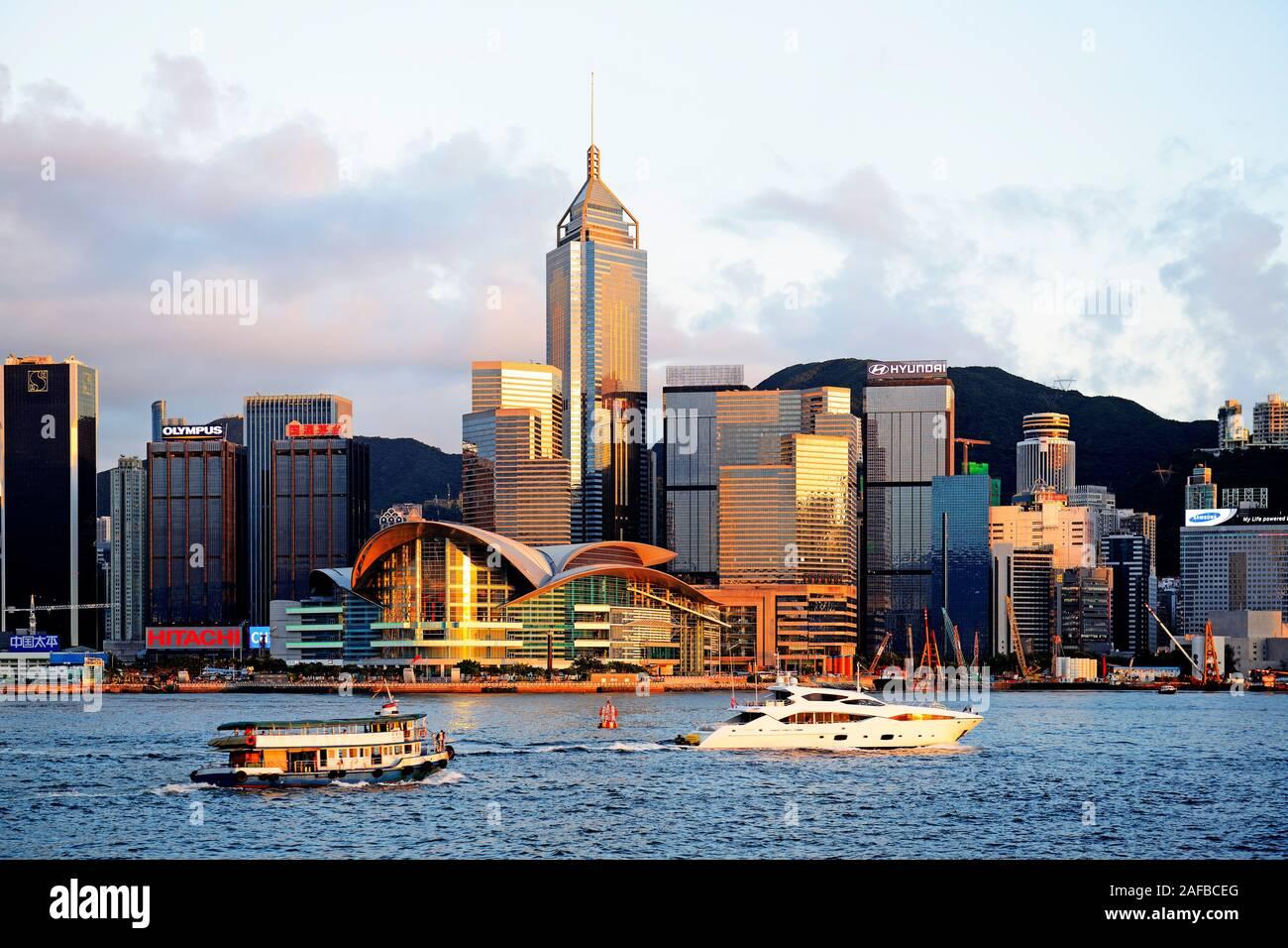 Blick von Kowloon bei Sonnenuntergang auf die Skyline auf Hongkong Island am Hongkong River, mit Booten auf dem Fluß, Central, mit dem International C Stock Photo