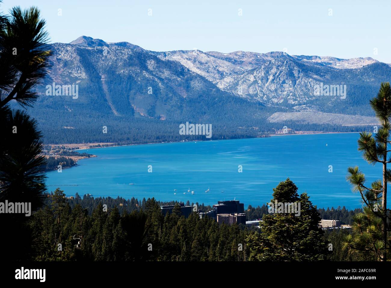 South Lake Tahoe And State Line Nevada Seen From Hills Through Trees With Mountains Stock Photo