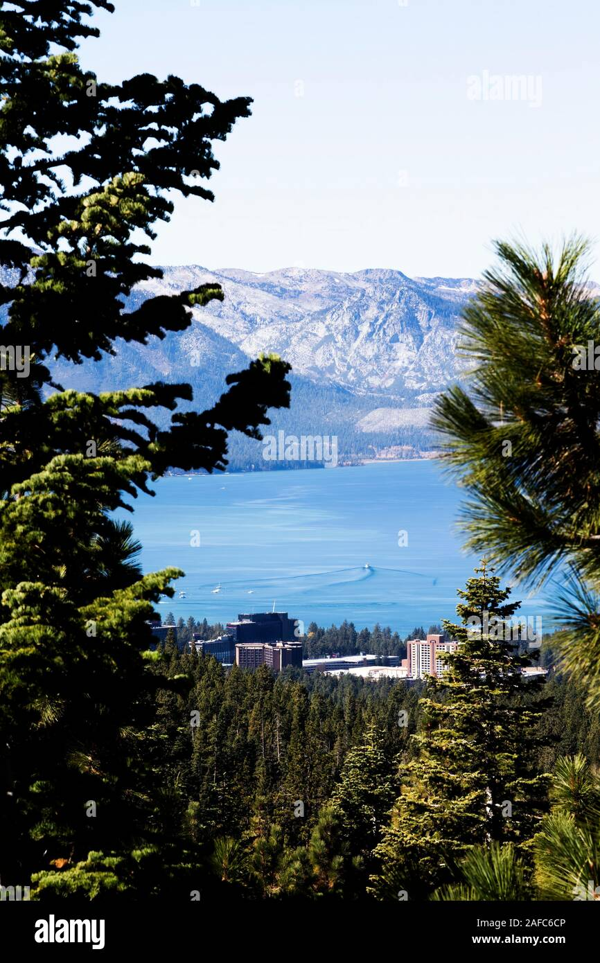 South Lake Tahoe And State Line Nevada Seen From Hills Through Trees With Mountains And Buildings Stock Photo